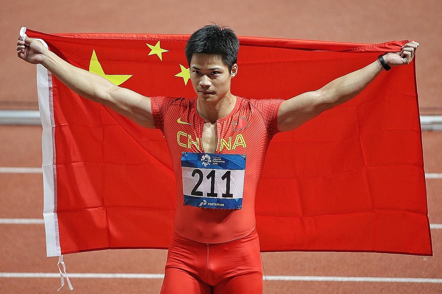 China's Su Bingtian carrying the Chinese flag after winning the men's 100m final in a Games record of 9.92sec, beating the old mark by 0.01 sec.