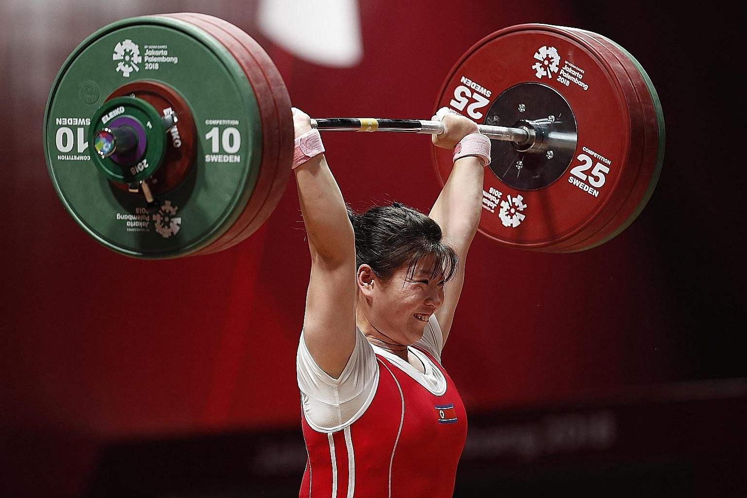 North Korea's Rim Jong Sim is all smiles as she lifts her way to the women's 75kg weightlifting gold medal yesterday, emulating younger sister Un Sim's feat on Saturday.