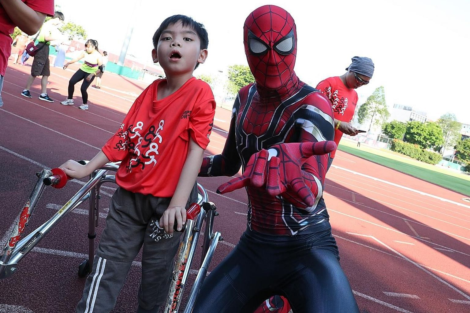 "Poo Jia Ming, eight, from the Cerebral Palsy Alliance Singapore School, with ""Spider-Man"" Neyton Tan, taking part in this year's Run For Inclusion, where athletes with disabilities run alongside the able-bodied."