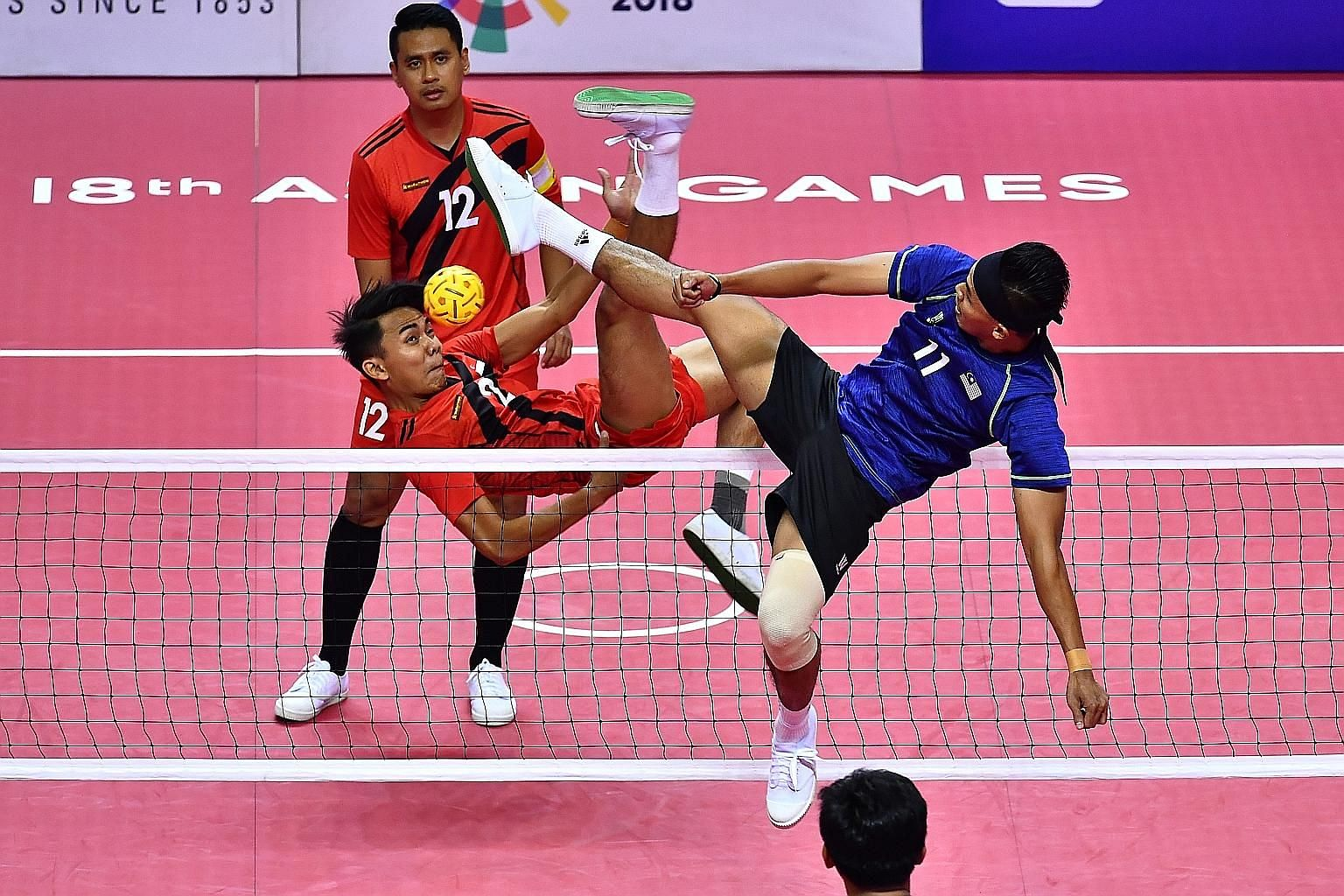 Singapore's Amran Mohamad Farhan (No. 12) and Muhammad A'fif Safiee (No. 2) in yesterday's regu semi-final, which Malaysia won 21-8, 21-8. The Republic shared the bronze medal with South Korea, the other losing semi-finalists.