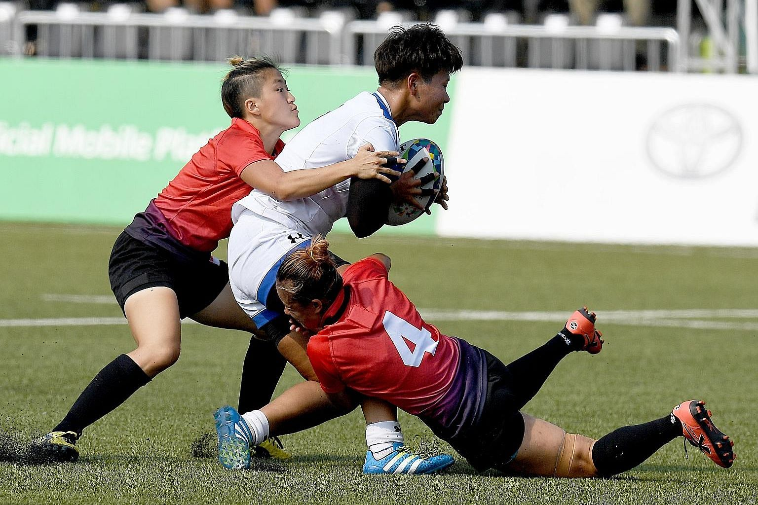 Jayne Chan (far left) and Eunice Chu tackling a South Korean. Chan played just five minutes but scored the winning try for Singapore's 22-17 Group A victory.
