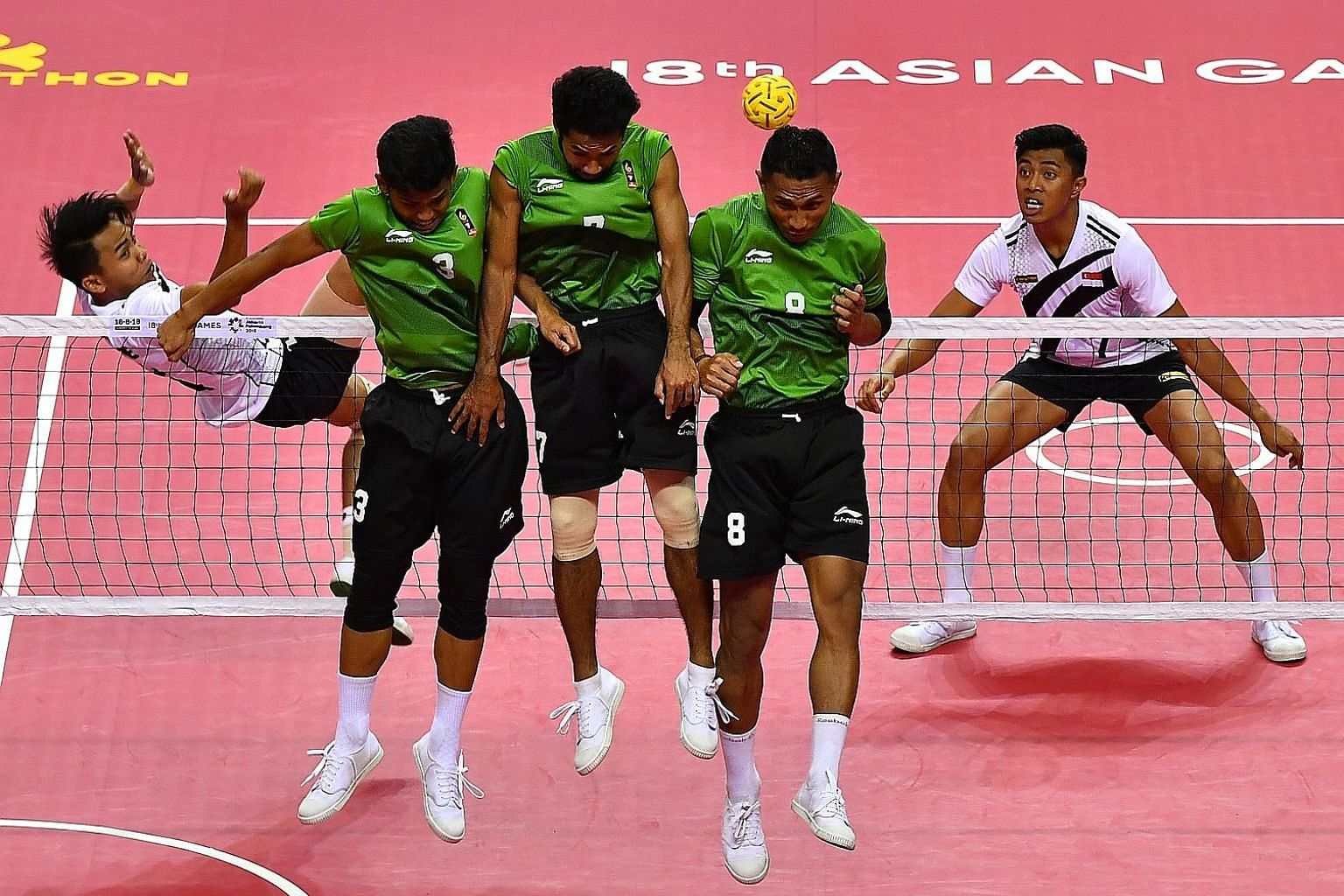 Singapore's A'fif Safiee (far left) and Khairilshamy Shamsudin find their way blocked by Indonesia in the sepak takraw men's quadrant semi-final yesterday. Singapore lost 21-8, 21-12 but earned a joint-bronze medal.
