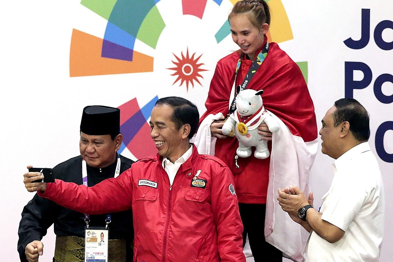 Indonesian President Joko Widodo and Indonesian Pencak Silat Association chairman Prabowo Subianto (far left) with Indonesian gold medallist Wewey Wita at the awards ceremony for the women's 50kg to 55kg Padepokan Pencak Silat event at the Asian Game