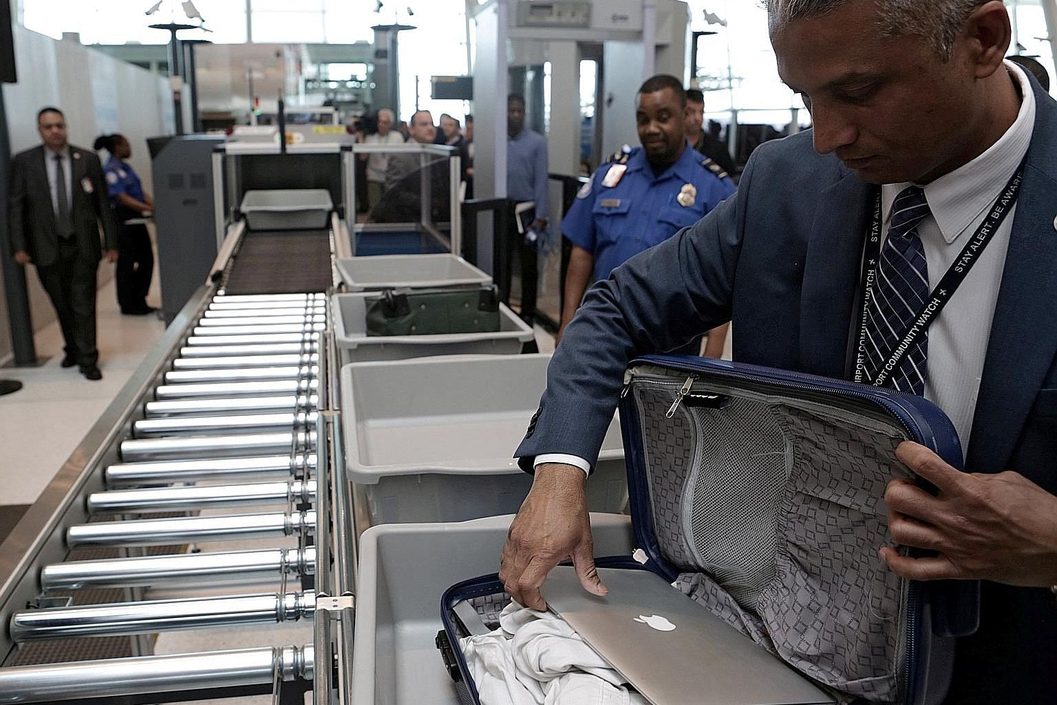Travellers, such as this man at JFK International Airport in New York, often deposit hand-carried and personal items in the security bins. Researchers said airports should offer hand sanitisers before and after each security checkpoint, and the bagga