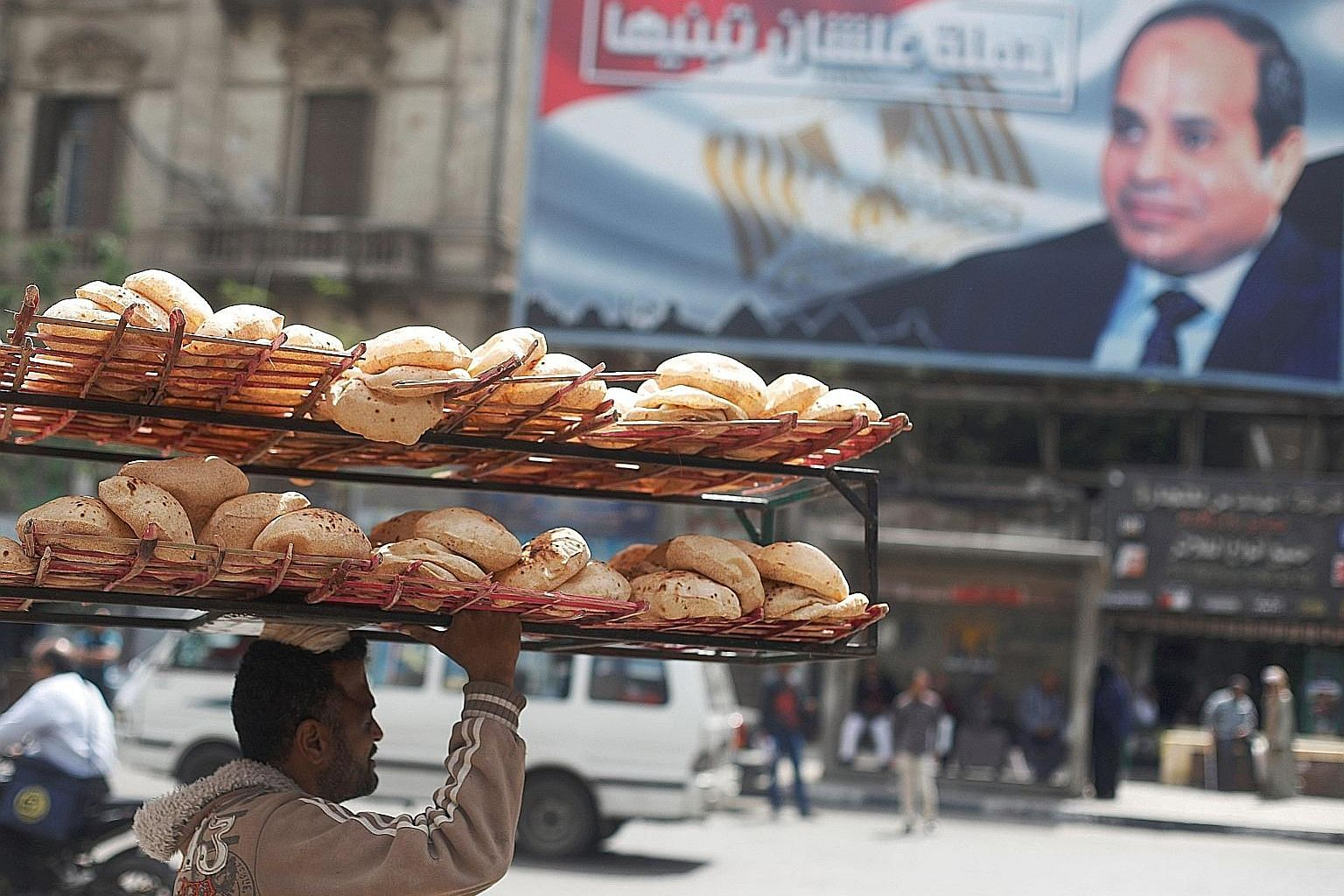 A bread seller walking past a banner featuring President Abdel Fattah el-Sisi. Egypt has seen a significant hike in inflation and a decline in purchasing power and living standards.