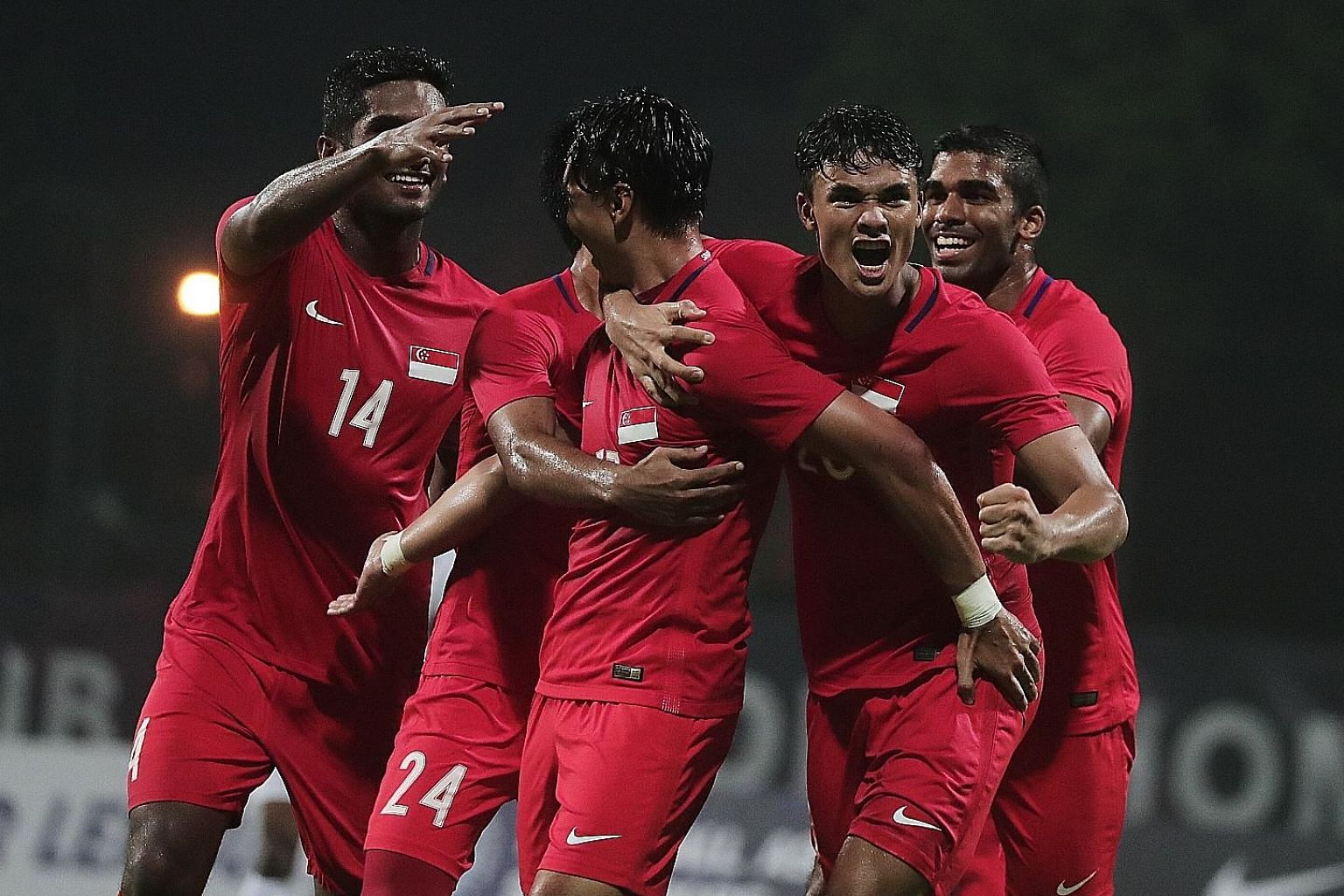 Singapore's players mob scorer Ikhsan Fandi (second from right) and the creator of his goal Shahril Ishak (centre) after the Lions' equaliser earned coach Fandi Ahmad a draw in his first match in charge.