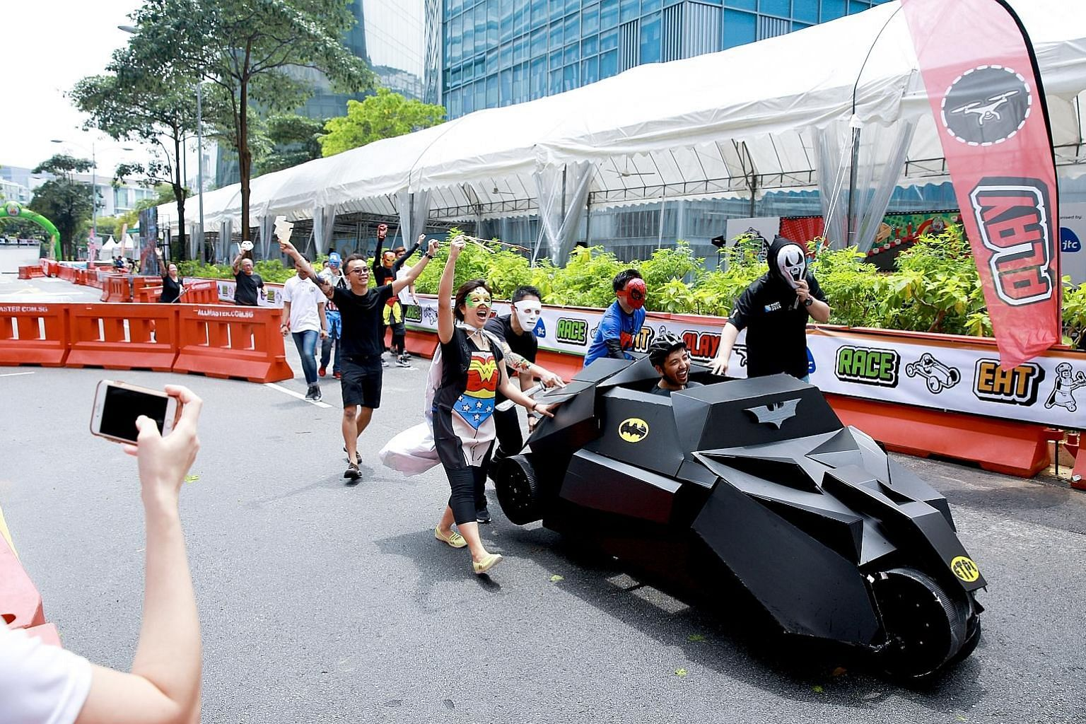 """A*Star Exploit Technologies employees, dressed as DC and Marvel comics superheroes, banding together yesterday to push their soapbox """"Batmobile"""" to the finish line."""