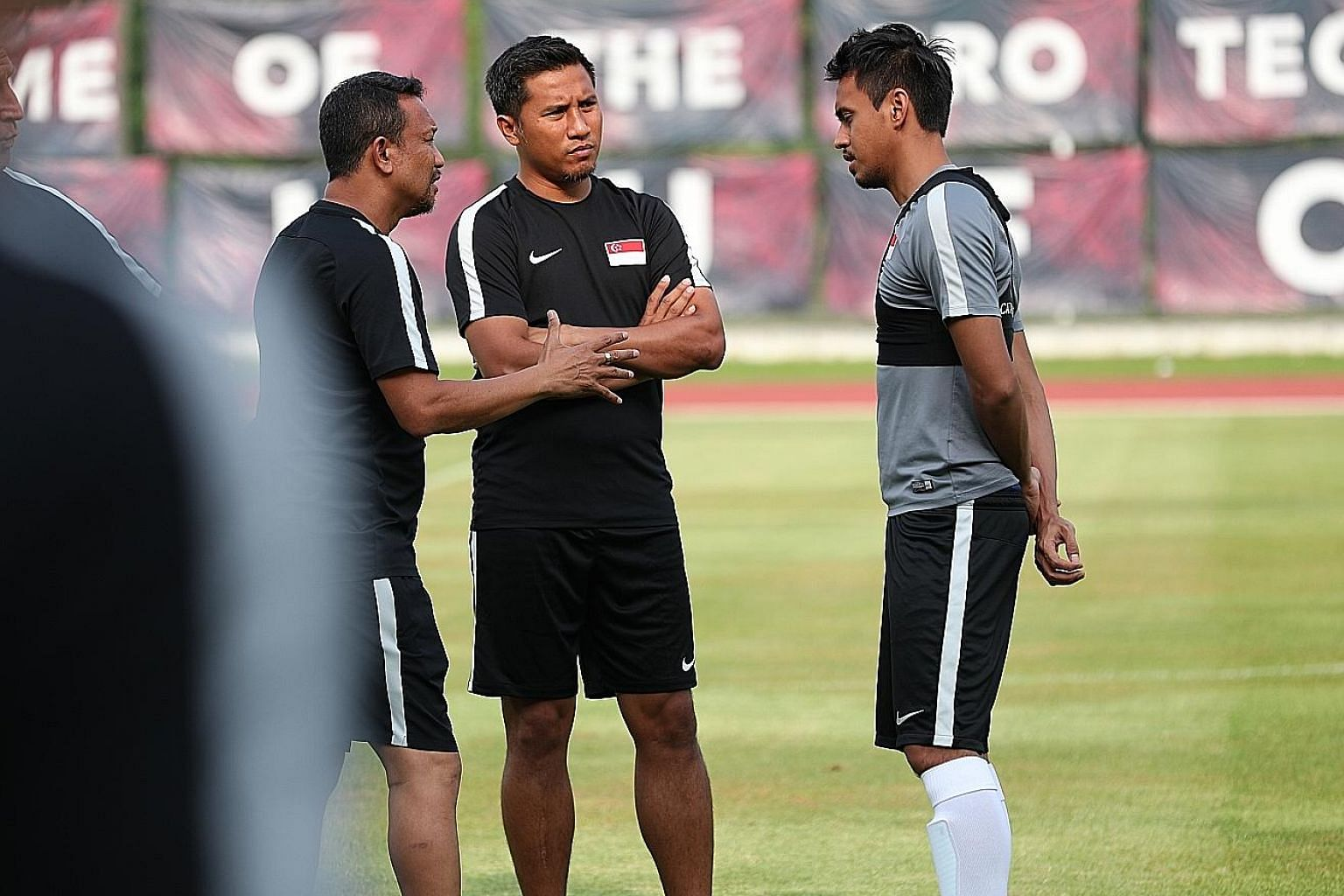 Singapore national football team head coach Fandi Ahmad and his player mentor Noh Alam Shah (centre) give midfielder Shahdan Sulaiman some advice during a Lions training session at Bishan Stadium.