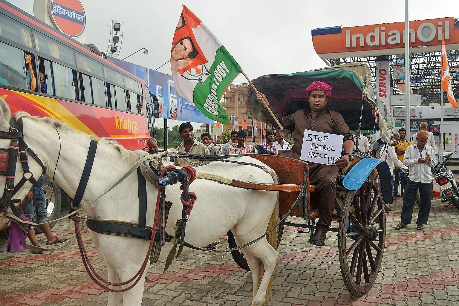 A Congress party activist holding a party flag and placard while sitting on a cart next to a petrol station in Ajmer yesterday during a nationwide strike called by the main opposition parties. The opposition is looking to tap public anger against Pri