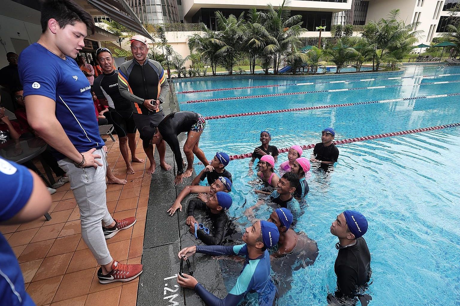 Olympic gold medallist Joseph Schooling sharing his experience with children from Care Singapore at Temasek Club yesterday.