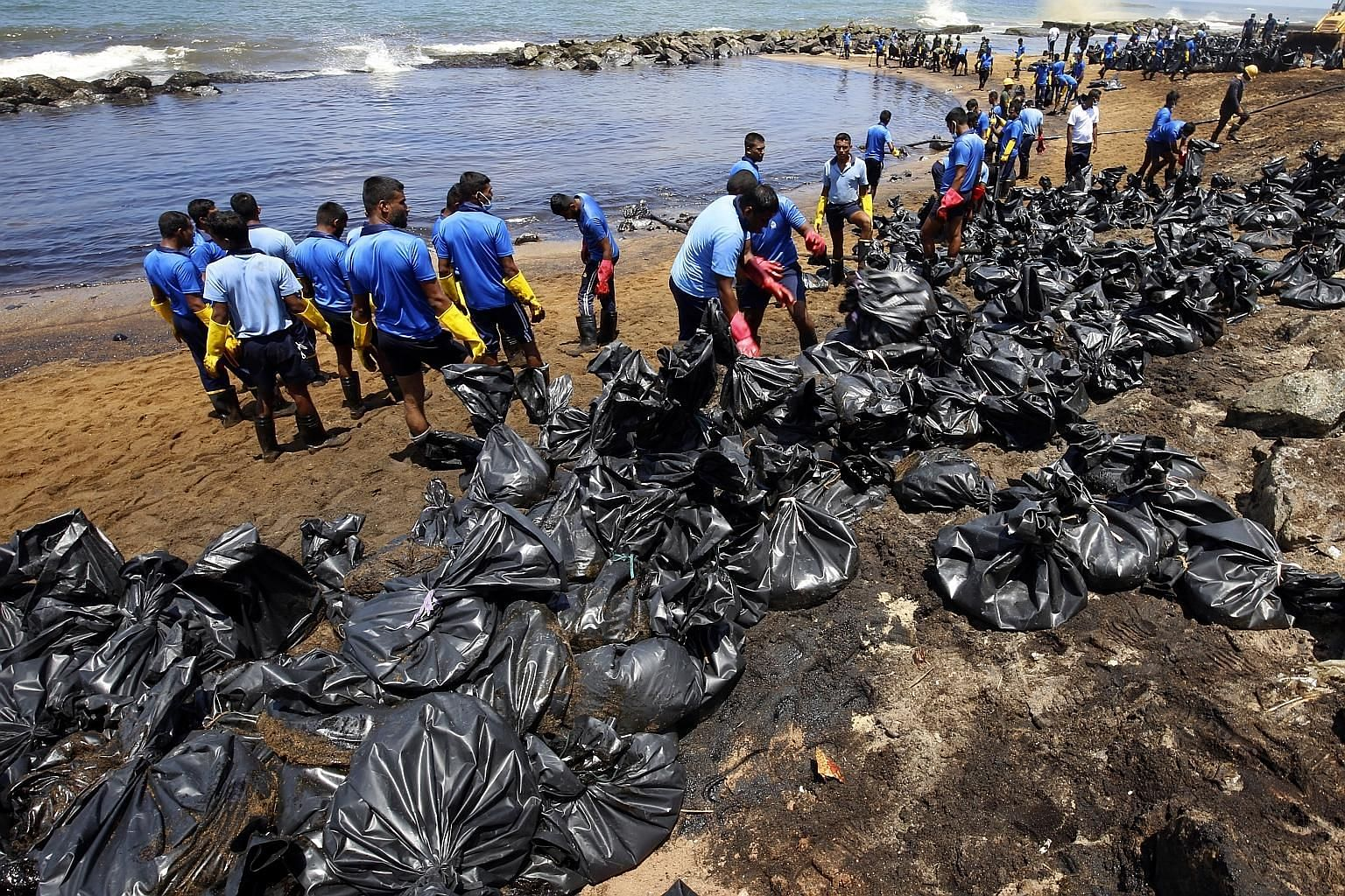 Sri Lankan navy personnel cleaning up an oil spill from a damaged pipeline on the shore off the north-western coast in Dikkowita, close to Colombo, on Tuesday. According to reports, a damaged ship-to-shore pipeline leaked fuel into the sea on Saturda