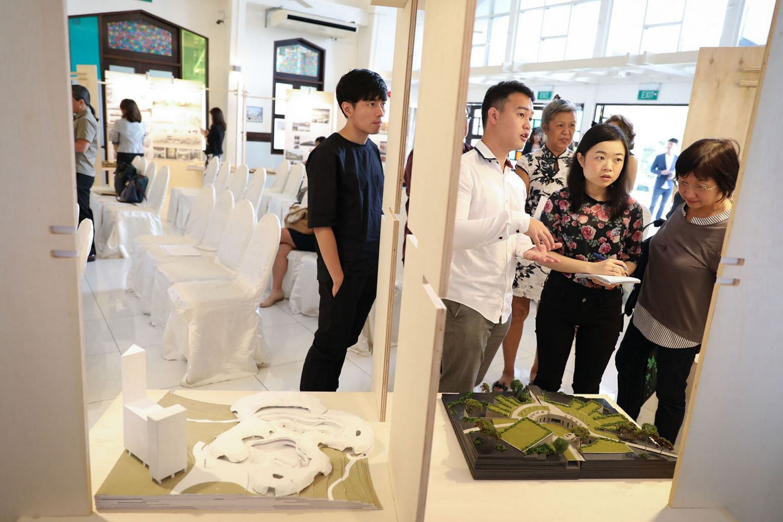 National University of Singapore architecture undergraduate John Kevin Chandra (in white), explaining his design that won the first prize in the Land For The Living - Space For The Dead design challenge yesterday. His design featured a proposed colum