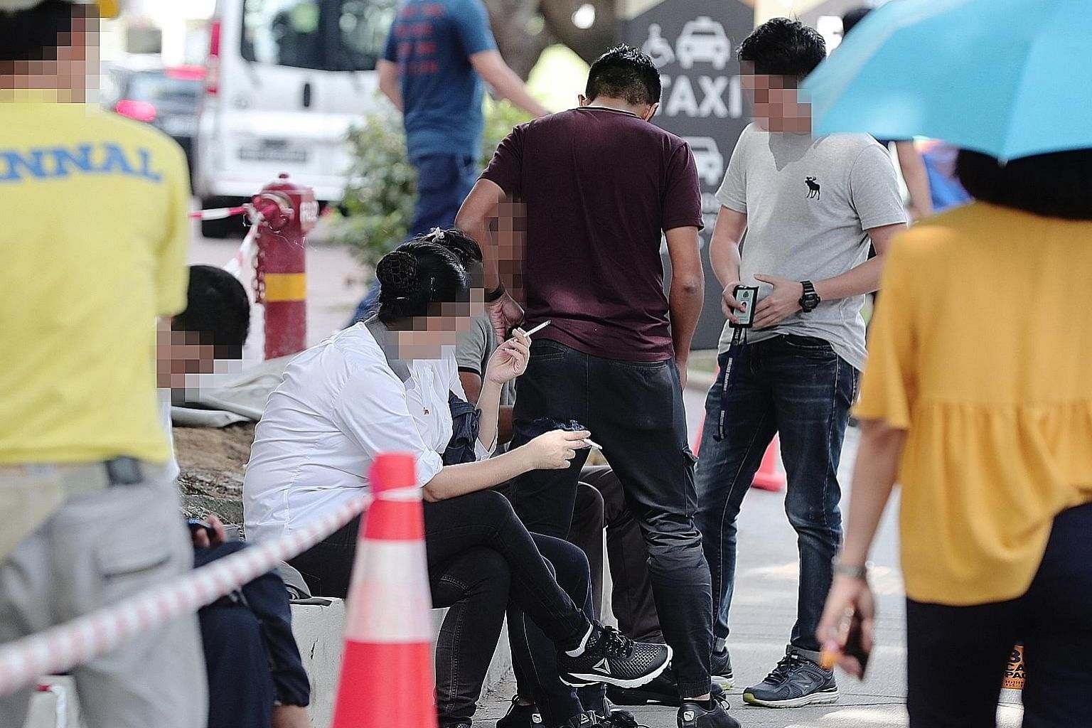 Singapore Customs officers checking whether people were smoking duty-unpaid cigarettes in Tampines Central. Offenders caught in the three-day operation were issued composition sums ranging from $500 to $1,200.
