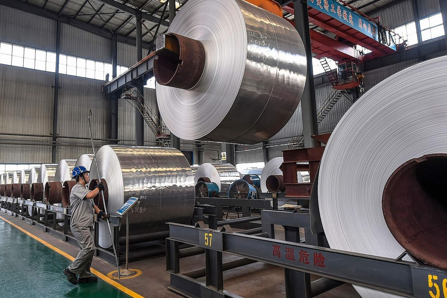 Rolls of sheet aluminium at a factory in Shandong province, China. Analysts say production of key goods such as motor vehicles and transport equipment continued to decline. Output of cars barely grew, while steel mills, aluminium smelters and oil ref