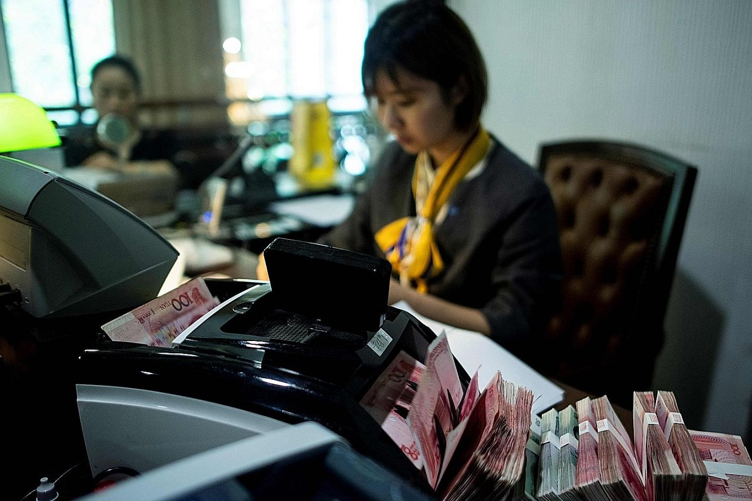 An employee using a currency counting machine at a Shanghai bank. China still boasts a strong foreign reserve position and has taken steps to cut debt.