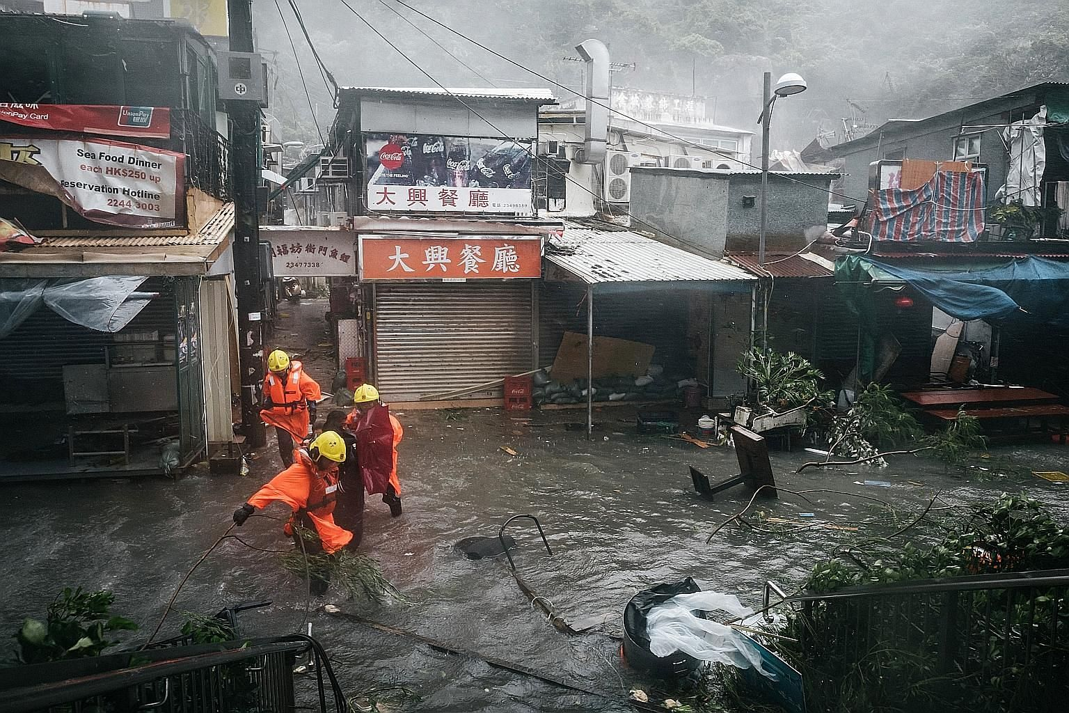 Firefighters escorting people through floodwaters as Typhoon Mangkhut lashed Hong Kong yesterday. The most powerful typhoon of the year was reported yesterday evening to be weakening as it moved deeper into southern China.
