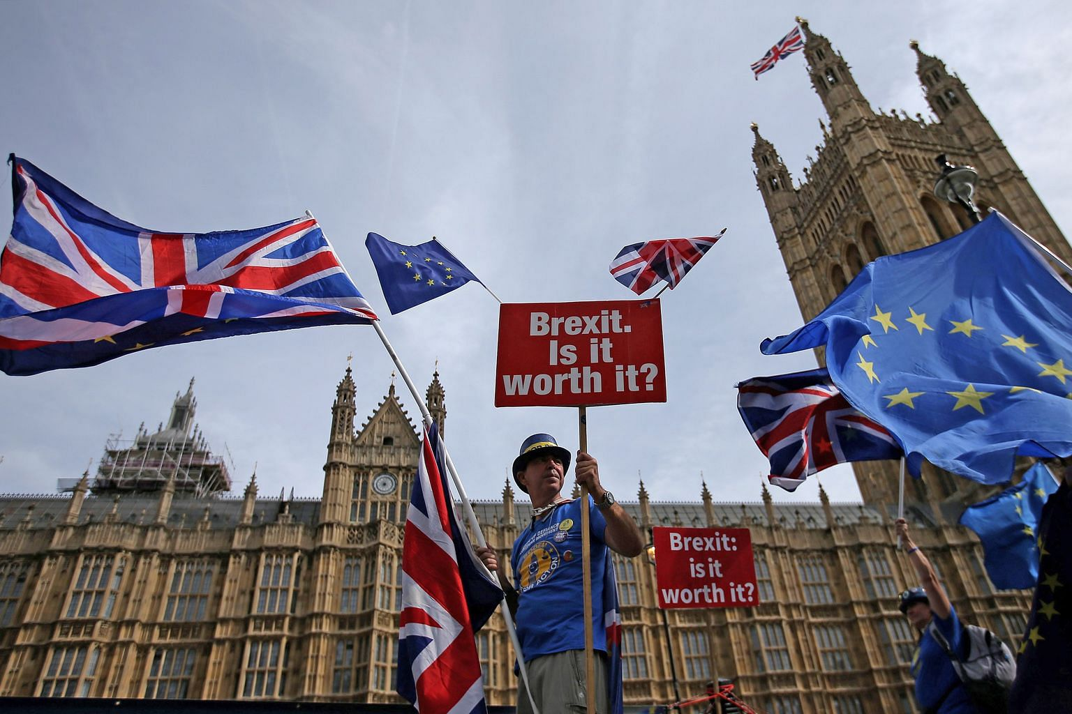 A demonstrator making his point while flying the British and European Union flags outside the Houses of Parliament in London earlier this month - six months before Brexit officially takes effect.