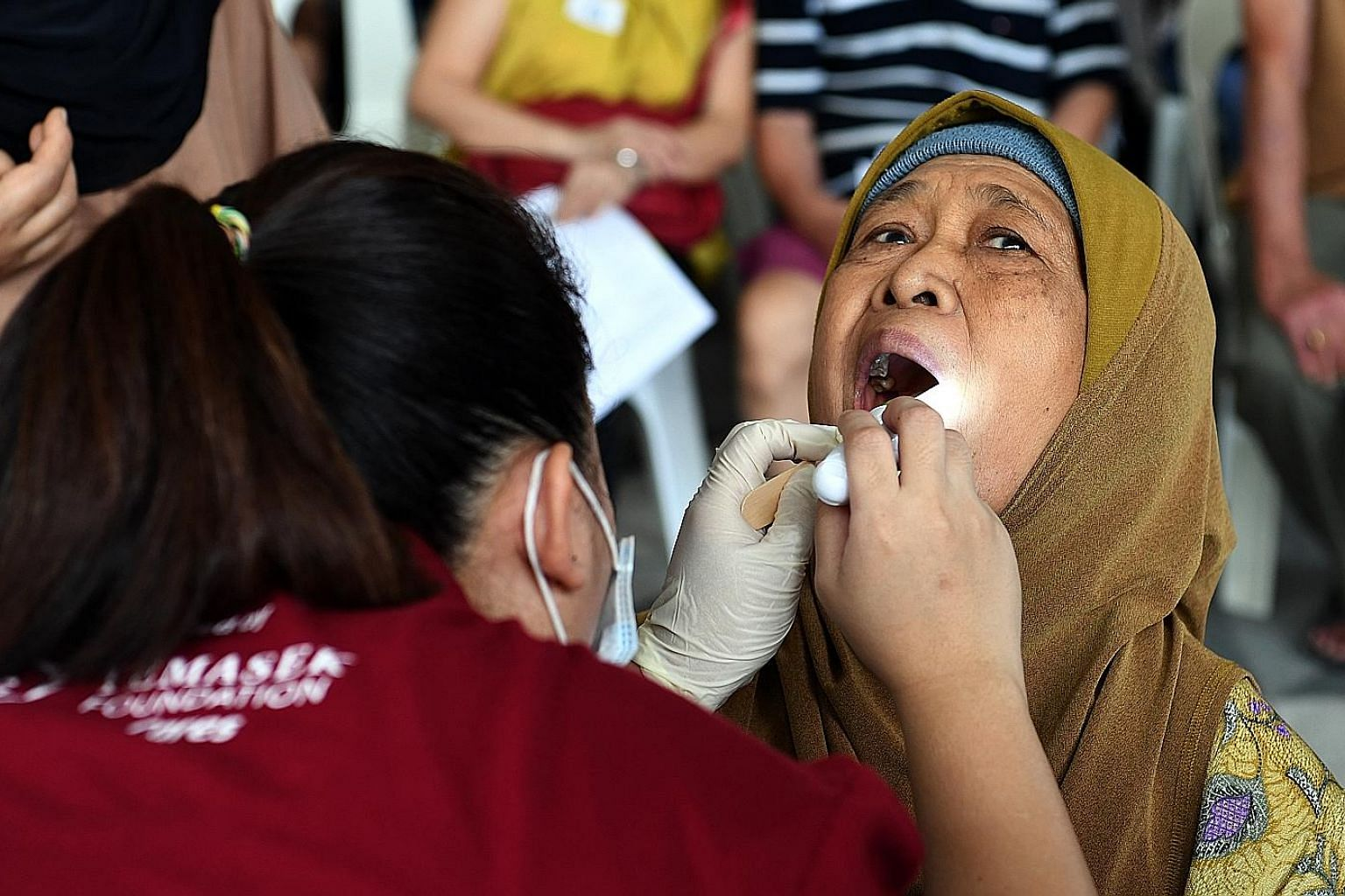 Madam Sudiah Sapii, 76, getting her teeth checked by a volunteer at a health screening yesterday at Kampung Admiralty, where Project Silver Screen was launched. Around 200 people from the neighbourhood took the chance to have their vision, hearing an