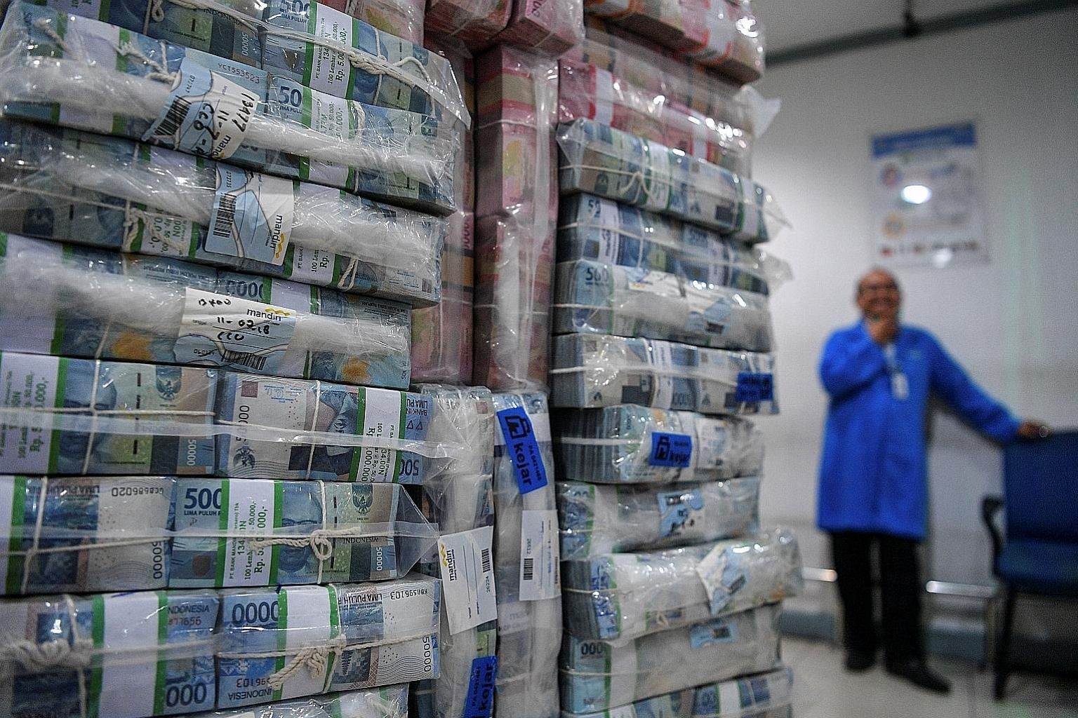 Stacks of Indonesian rupiah banknotes at Bank Mandiri's headquarters in Jakarta. The sharp drop in the currency - caused by a widening current account deficit and further weakened by US-China trade tensions - has prompted Indonesia to consider measur