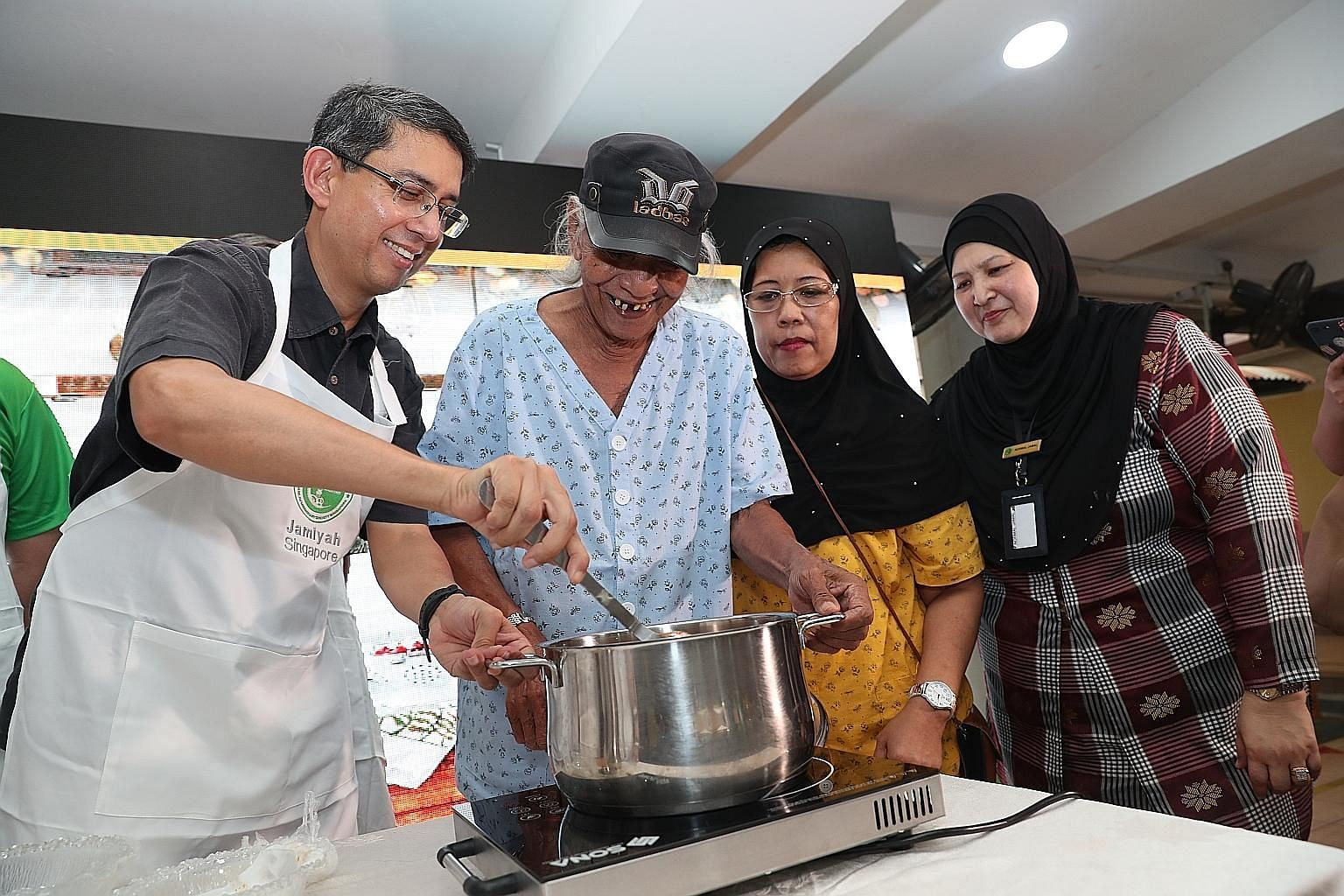 Guest of honour Muhammad Faishal Ibrahim trying his hand at making Bombay curry chicken, one of the recipes from the book, with the help of Jamiyah residents Jambaree Ahmad and Suriah Wakee Yon, and staff member Normal Jamal.