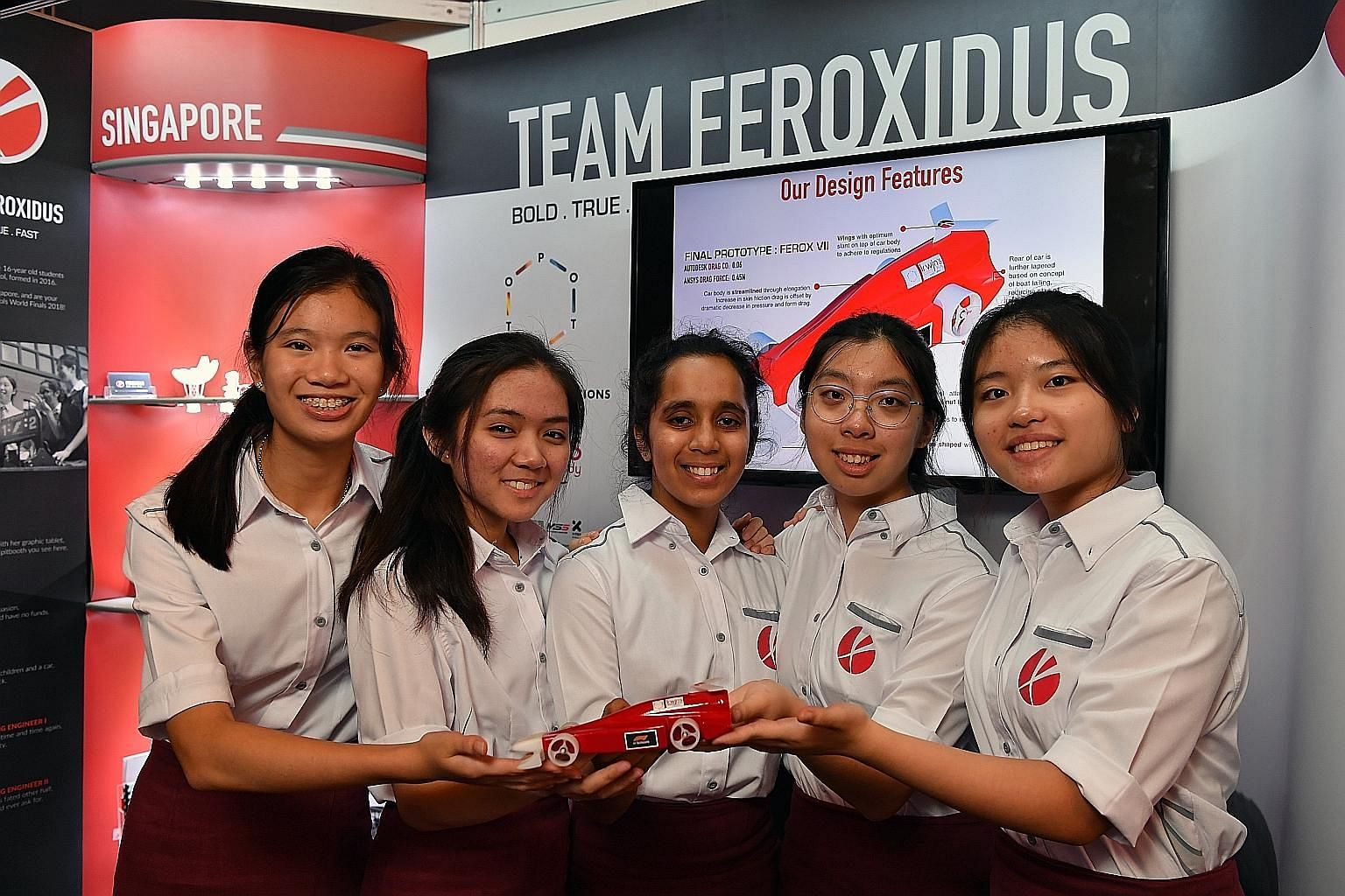 (From left) Nicole Lee, Kirsten Negapatan, Harshita Chauhan, Angeline Lai and Charisse Kwong of Raffles Girls' School showing off their car. They took part earlier this month in the world finals of the F1 in Schools competition, said to be a test of