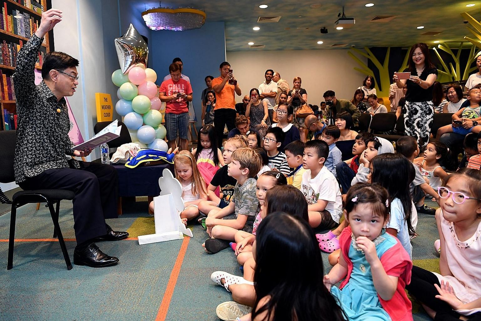 Finance Minister Heng Swee Keat reading to children about the life of Singaporean scientist Chou Loke Ming at the launch of the Asian Scientist Junior Book Series, a children's book series featuring six scientists from Asia.