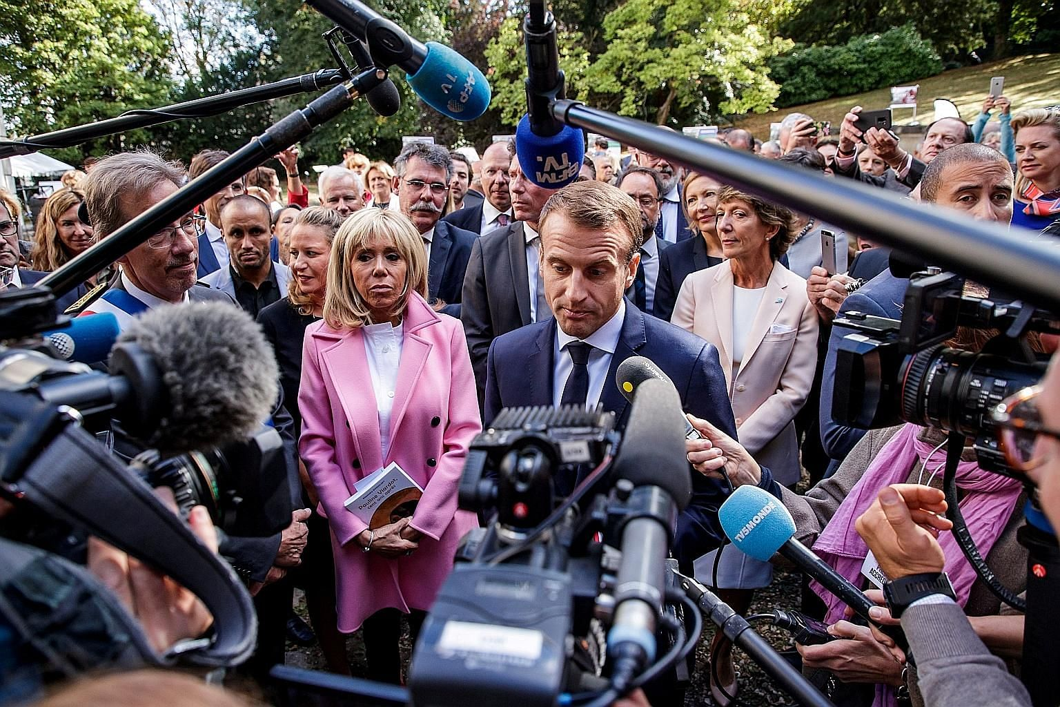 French President Emmanuel Macron speaking to the press as his wife, Brigitte, looks on during a visit to Bougival, near Paris, earlier this month. Mr Macron's approval rating has plunged to only 19 per cent, with 60 per cent finding his achievements