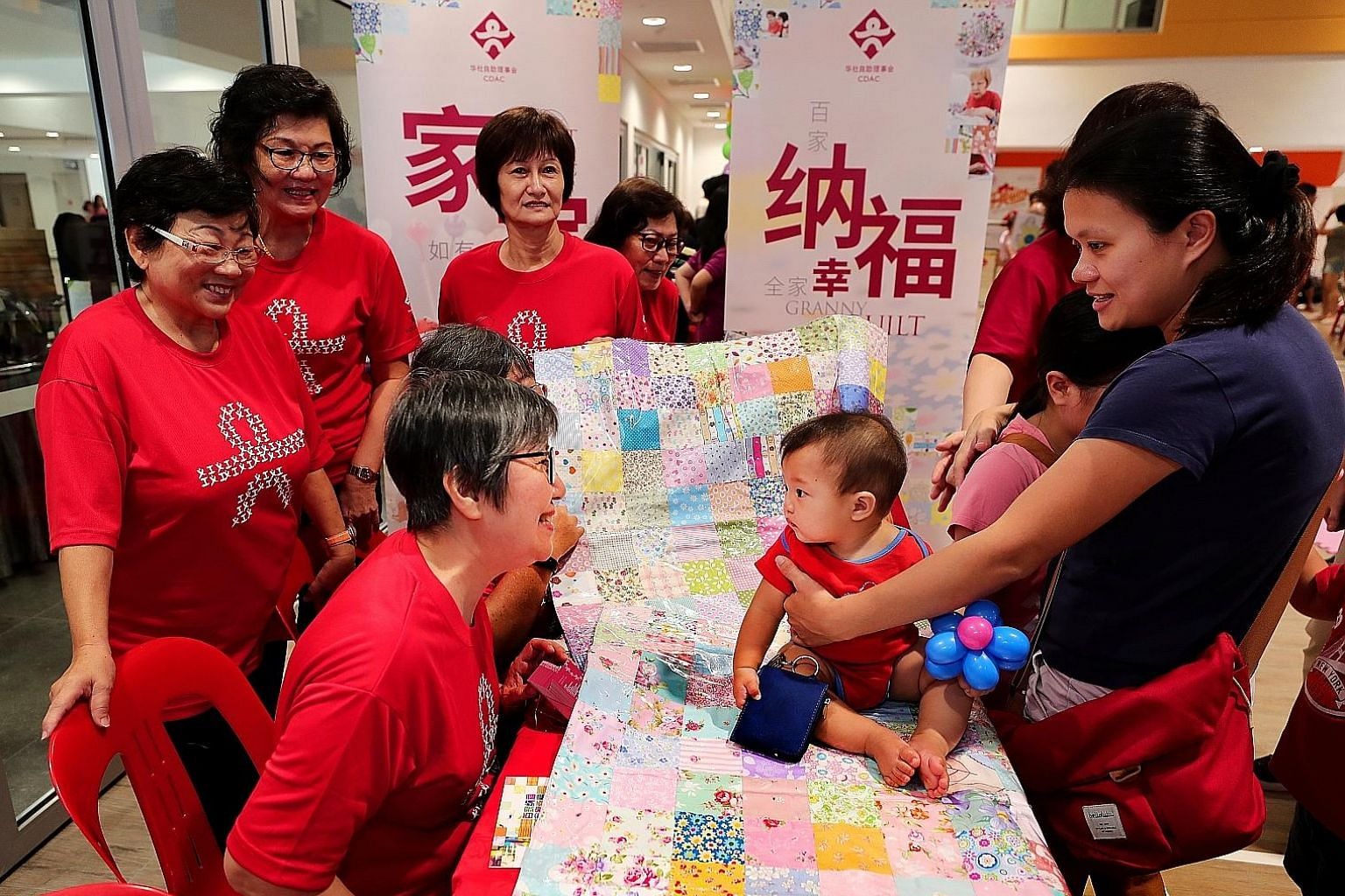 Housewife Amy Loh (right), 35, with her seven-month-old baby, Ajay Tan, at the booth of the Granny Quilt Project at Radin Mas Community Club yesterday. The Chinese Development Assistance Council (CDAC) piloted the Granny Quilt Project in August last