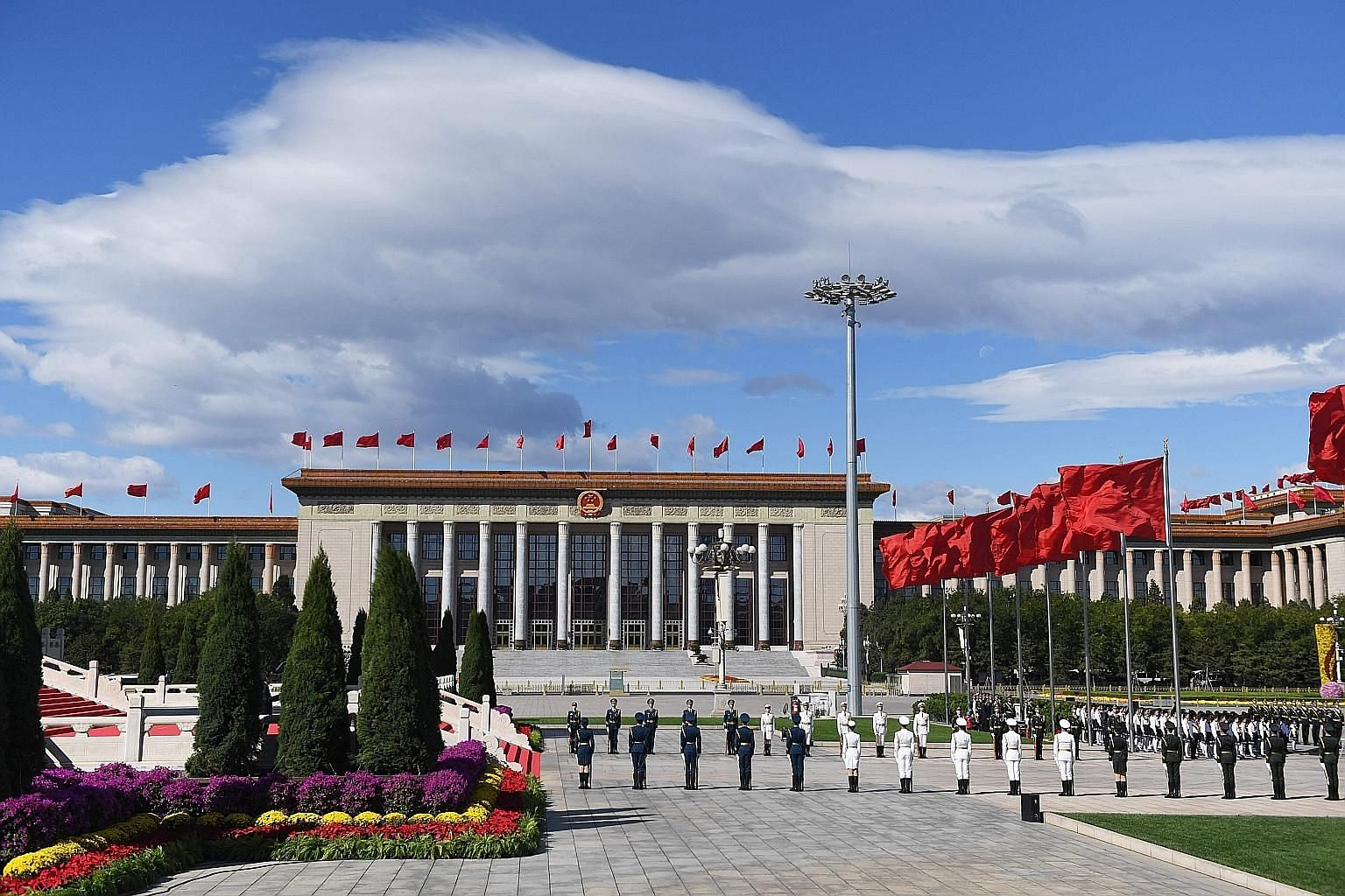 A military honour guard at Beijing's Tiananmen Square during a ceremony yesterday, on the eve of China's national day, when Chinese leaders honoured those who lost their lives serving the country and laid wreaths at the Monument to the People's Heroe