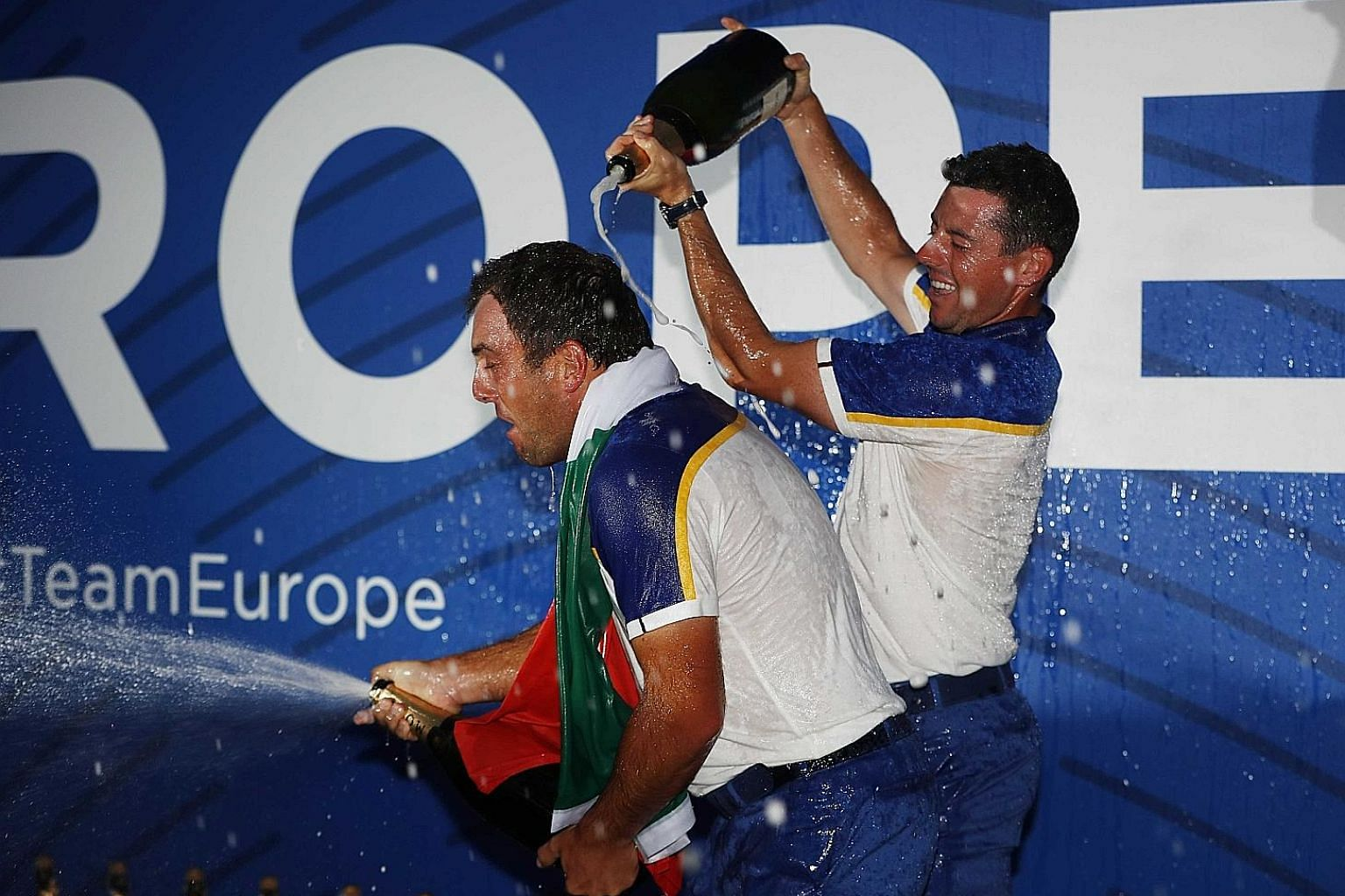 Team Europe's hero Francesco Molinari spraying the bubbly after their thrashing of the US at Le Golf National as Rory McIlroy pours more champagne on him.