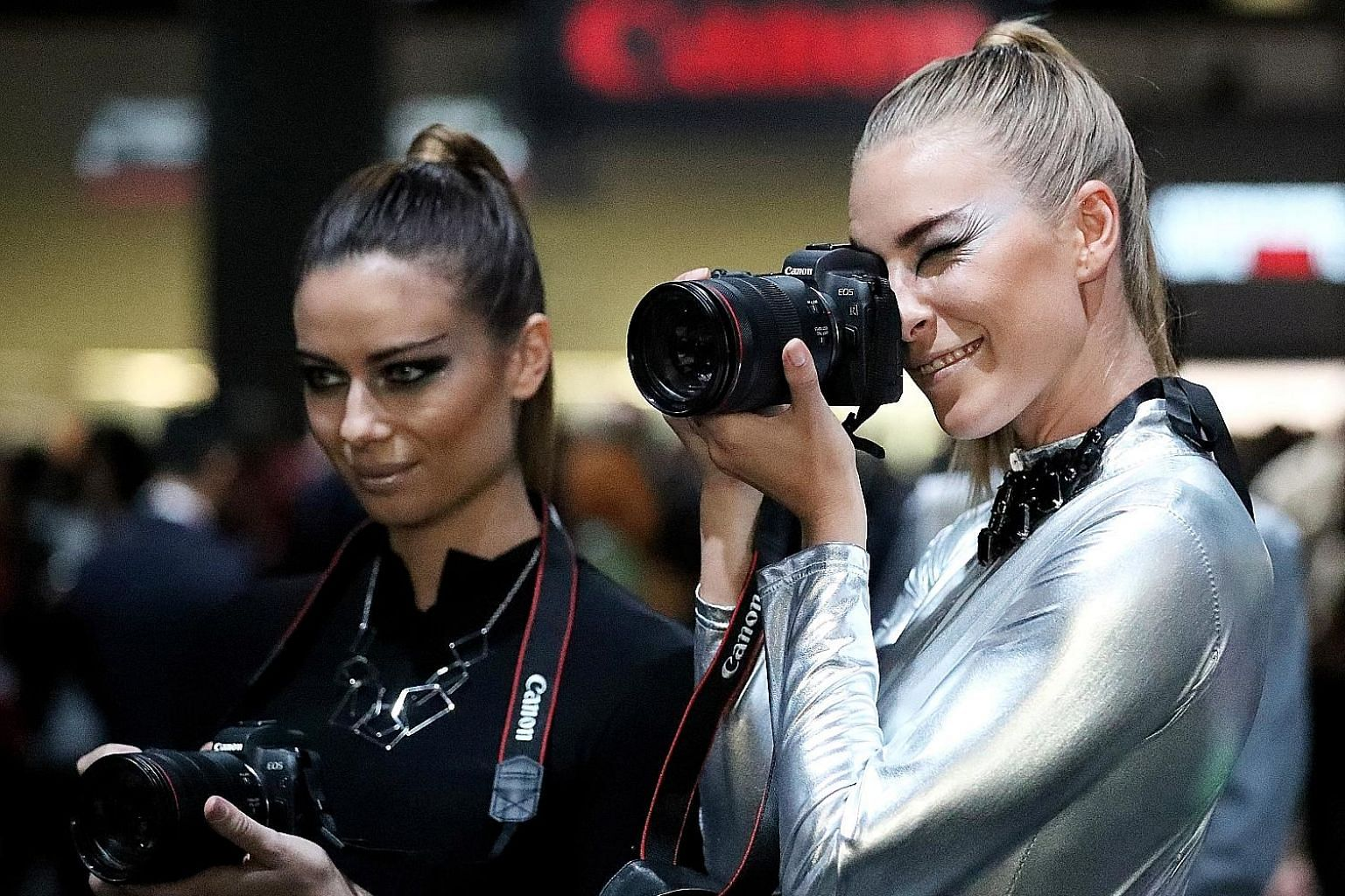 Models with Canon's first full-frame mirrorless digital camera, the EOS R, at Photokina 2018 in Cologne, Germany, last month.