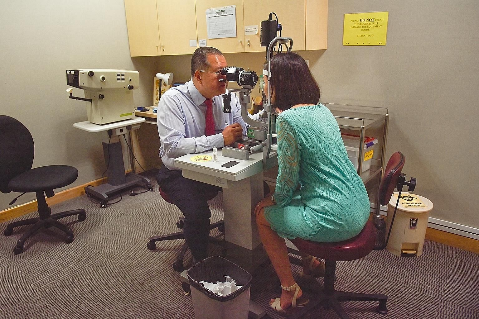 Professor Aung Tin demonstrating an eye examination on a slit lamp machine. While overseas studies have found a link between myopia and glaucoma, it is the first time this link has been found here, says Prof Aung, who was involved in the local studie