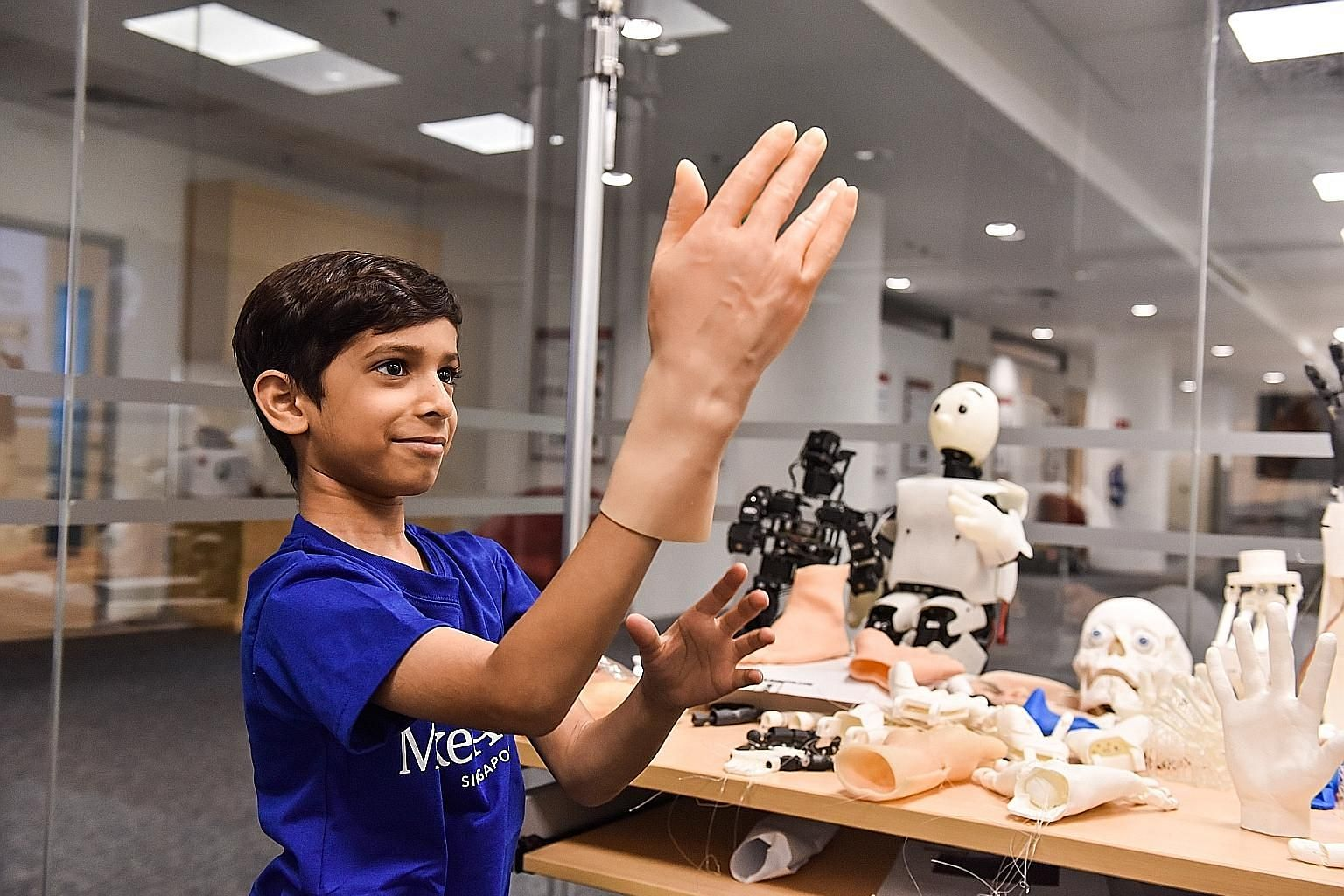 "Zahaan Tambawala meeting Poppy, a customised robot, yesterday. He also tried on artificial skin (right) designed for robots. The aspiring ""robot builder"", who had been battling cancer, celebrated his one-year anniversary of defeating the disease with"