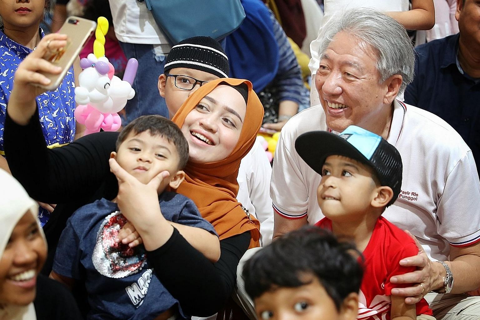 Deputy Prime Minister Teo Chee Hean having his picture taken with a family at the Malay Cultural Village event yesterday.