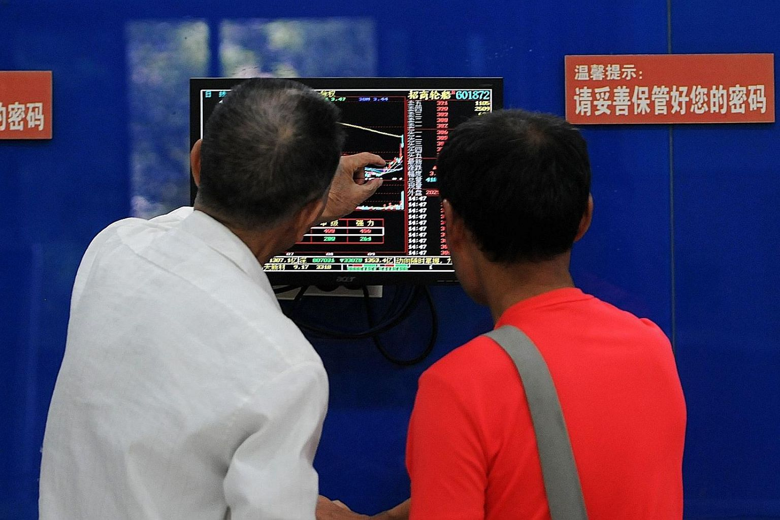 Investors monitoring stock prices in Jiujiang, Jiangxi province, yesterday. Foreigners yesterday dumped 9.7 billion yuan (S$1.96 billion) of A shares through exchange links with Hong Kong.