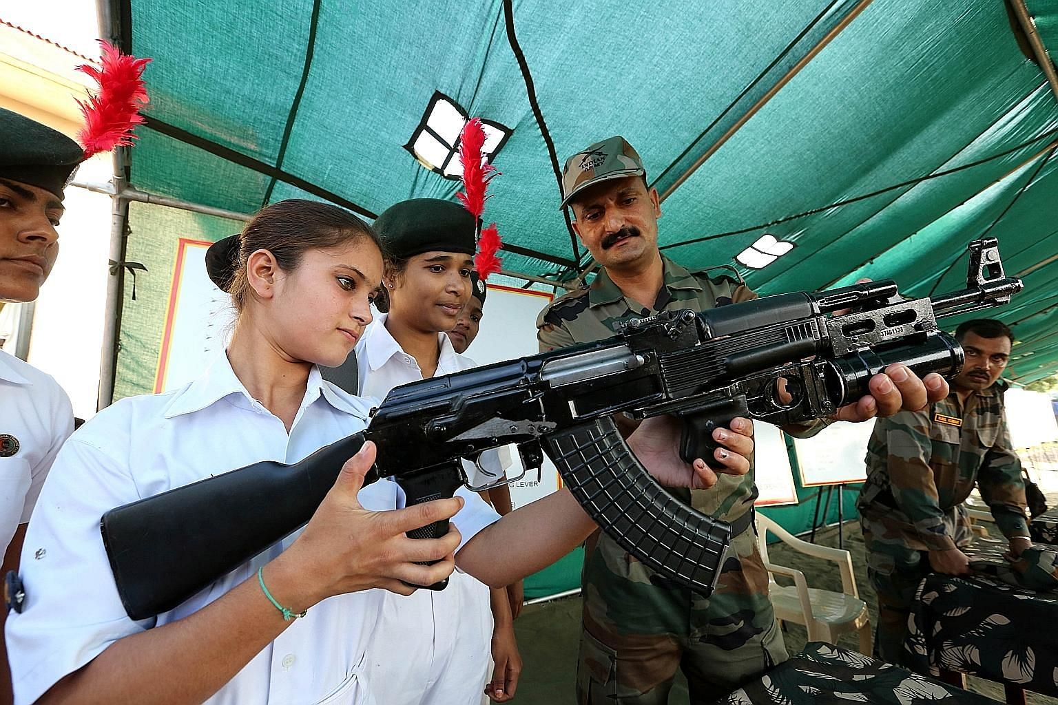 An Indian army soldier explaining how an AK-47 assault rifle works to National Cadet Corps members during Parakram Parv celebrations in the central Indian city of Bhopal on Sept 29. The celebrations mark the second anniversary of an attack by the Ind