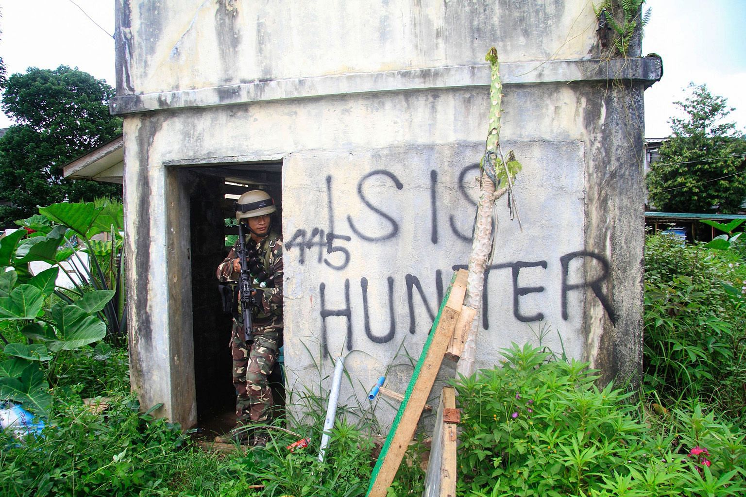 A Philippine soldier taking cover during the Marawi siege. Even as ISIS' footprint shrinks in Iraq and Syria, it is making inroads to existing and emerging conflict zones, including Asia. Extremists continue to travel to South-east Asia to join ISIS-