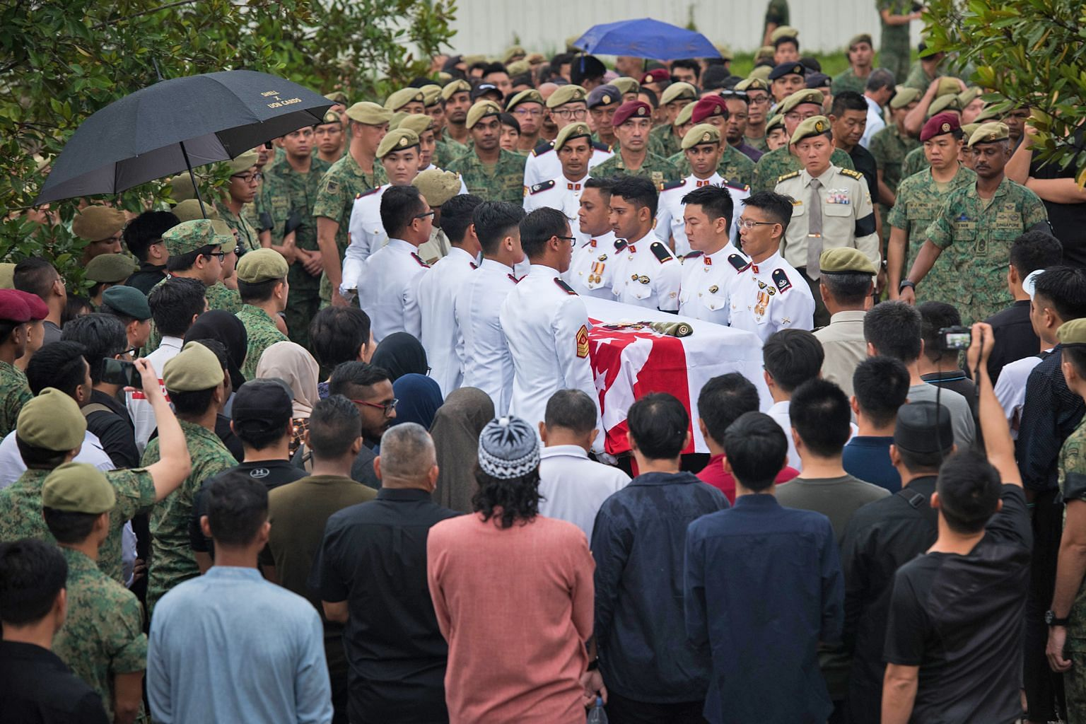 Above: 3WO Muhammad Sadikin Hasban's wife Norsidah Kamilan (facing camera) being comforted during the funeral. Left: The body of 3WO Sadikin being transferred to the burial site at Lim Chu Kang Muslim Cemetery yesterday.