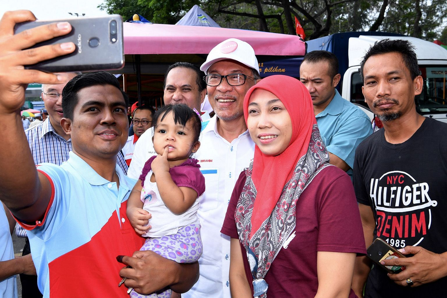 Datuk Seri Anwar Ibrahim (centre) posing for a photo with visitors at the Bagan Pinang Farmers' Market in Port Dickson yesterday. While Mr Anwar's victory in Saturday's by-election in the town is not in question, what will be closely watched is his m