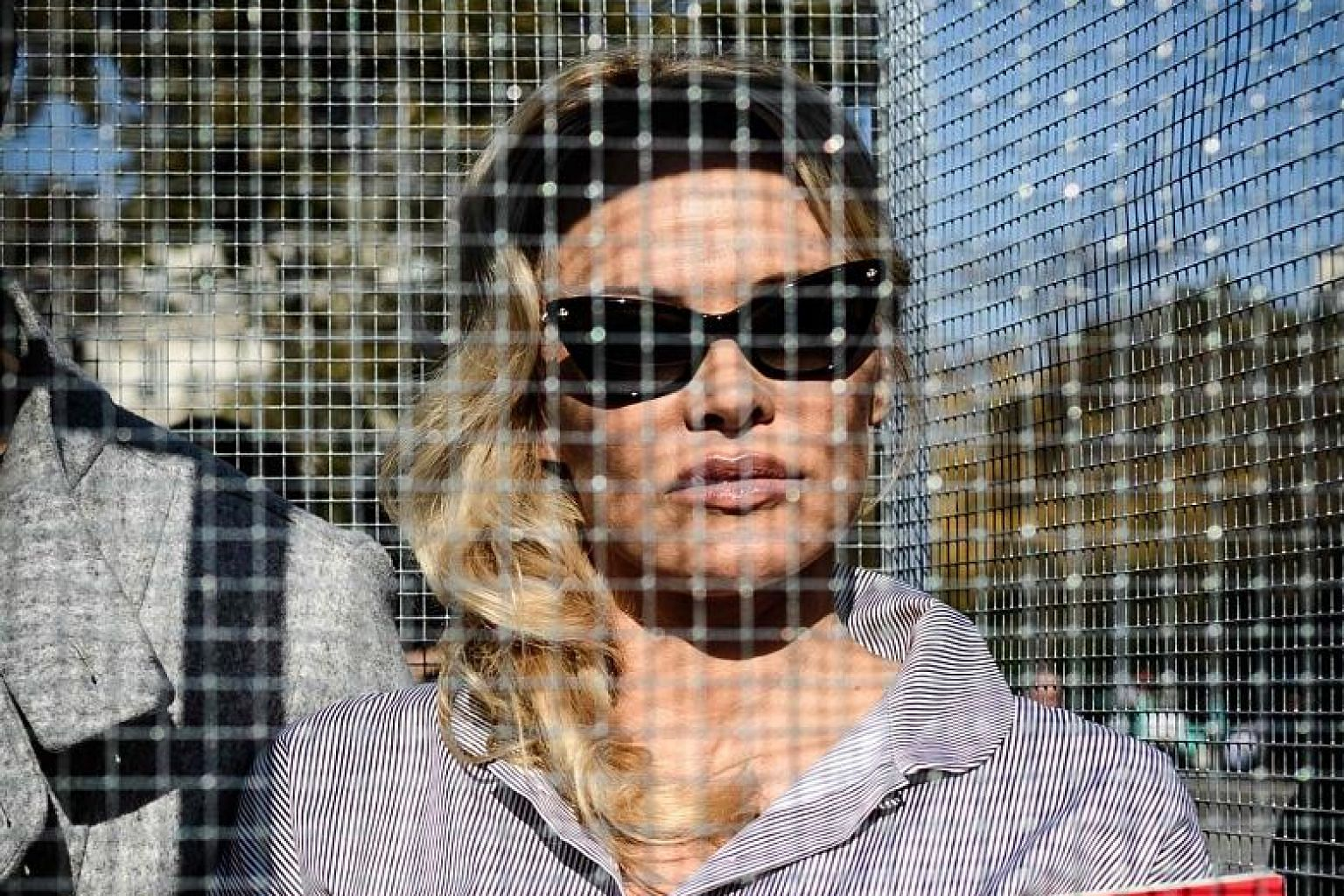 Actress Pamela Anderson stands in a cage displaying a placard against the caging of animals at an event organised by Compassion in World Farming in Paris.
