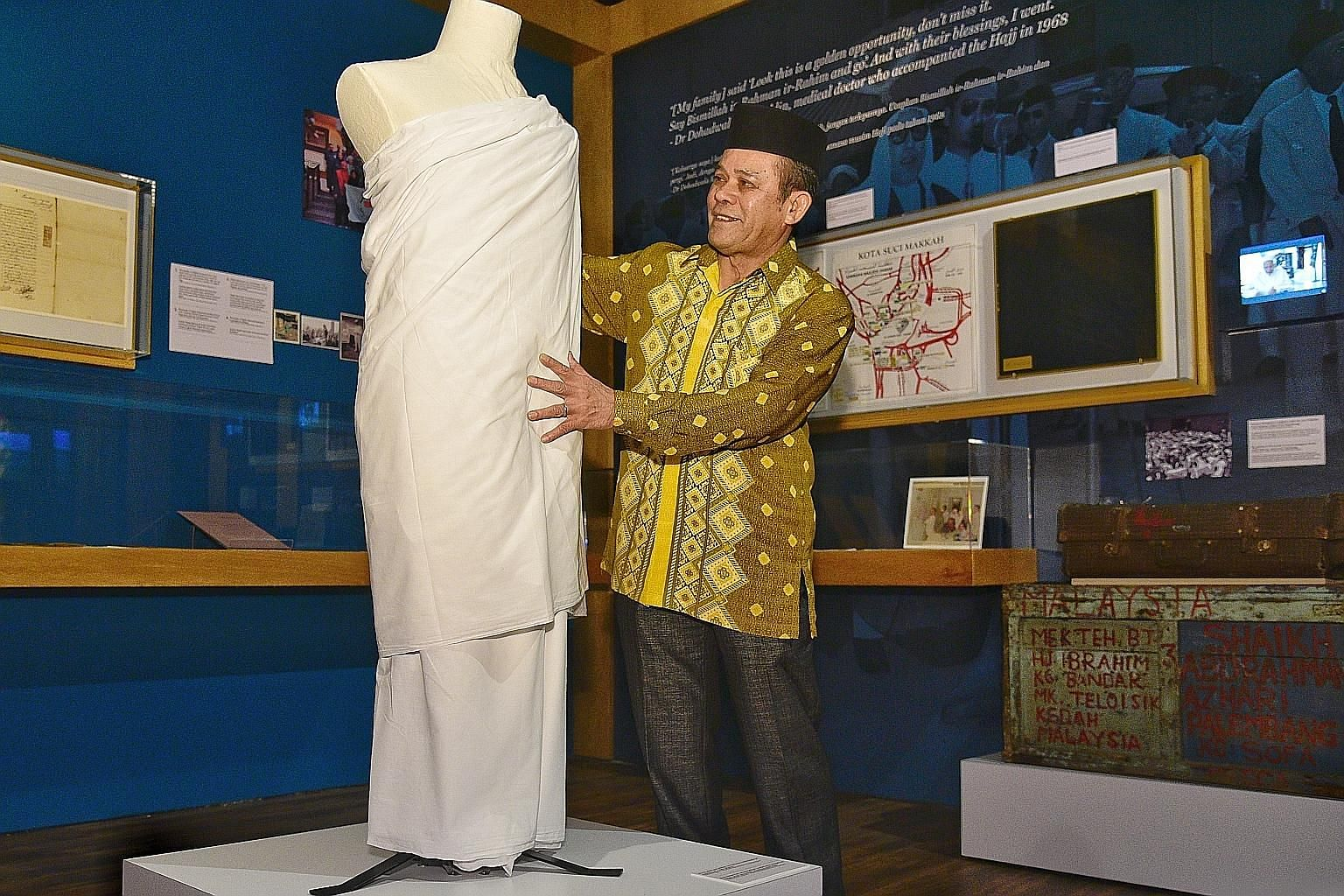 Mr Abdul Halim Mohamed Amin, the former head of haj services with Muis, with the display of his ihram and pelikat sarong, worn by male pilgrims to Mecca, which he donated for the exhibition at the Malay Heritage Centre in Kampong Glam.