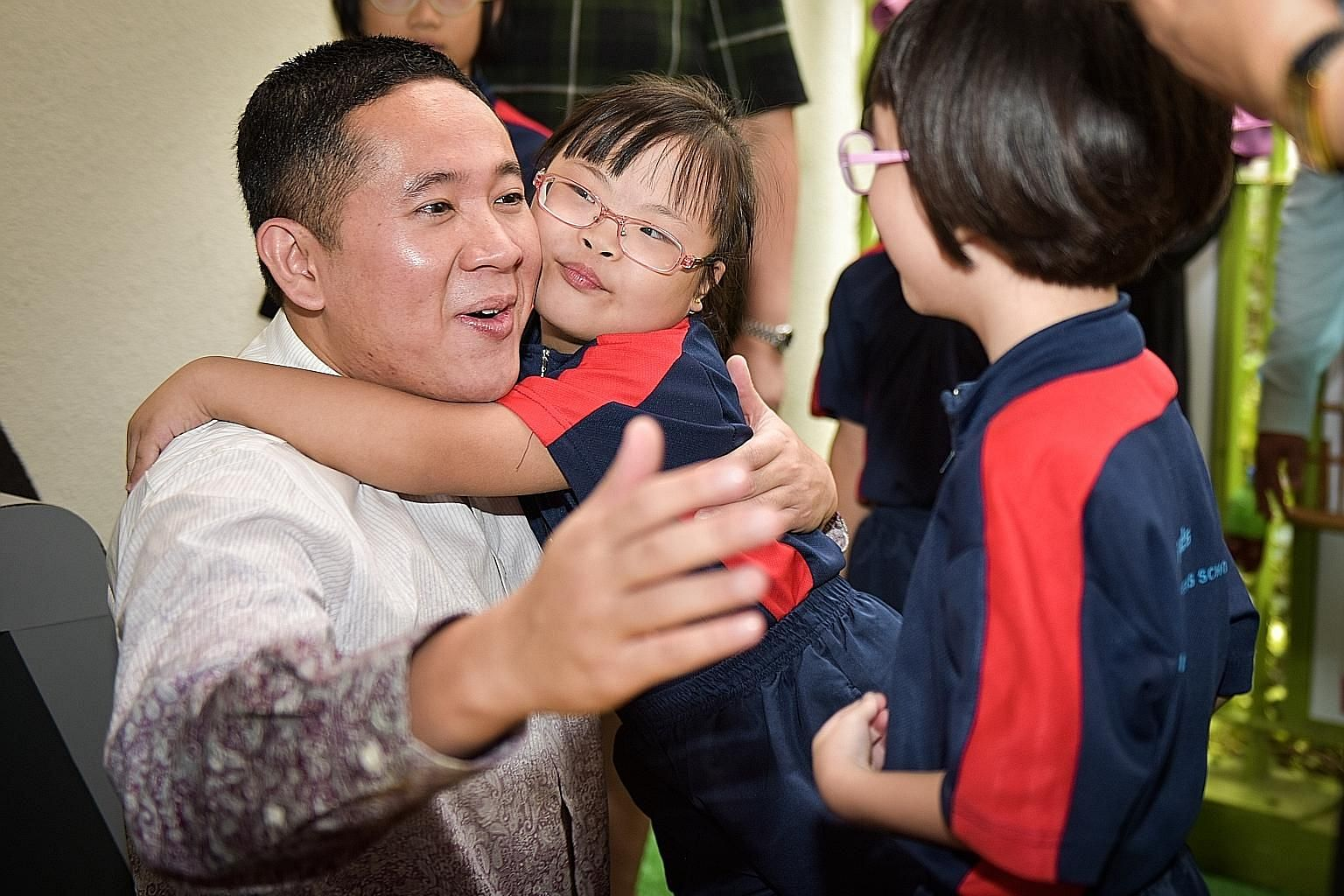 Amanda Wang, eight, giving a surprise hug to Mr Amrin Amin, Senior Parliamentary Secretary for the ministries of Home Affairs and Health and an MP for Sembawang GRC, who was the guest of honour at Woodlands Gardens School's 50th anniversary celebrati