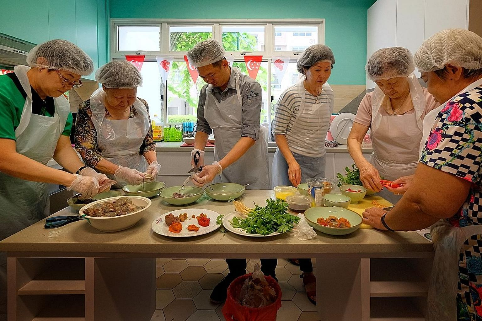 Trainees (from left) Hoo Jan Wah, 77, Tan Soi Noi, 60, Ng Siew Tim, 60, Heng Tang Kwee, 69, and Chia See Moy, 68, watch intently as Mr Wang (not in photo) stirs assam paste in the wok. Some of them cover their faces with cloth as the chilli from the