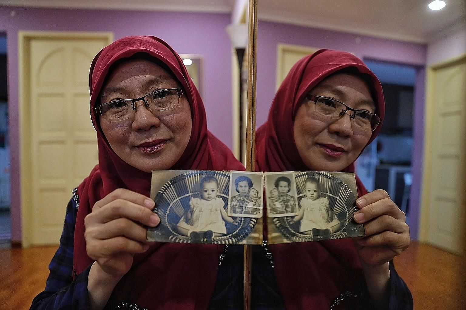 Madam Zahara Abdullah with her baby photos, including one taken with her late adoptive mother Habsah Masagos Omar. She also has adoption documents and her birth certificate, but they do not carry her birth parents' names.