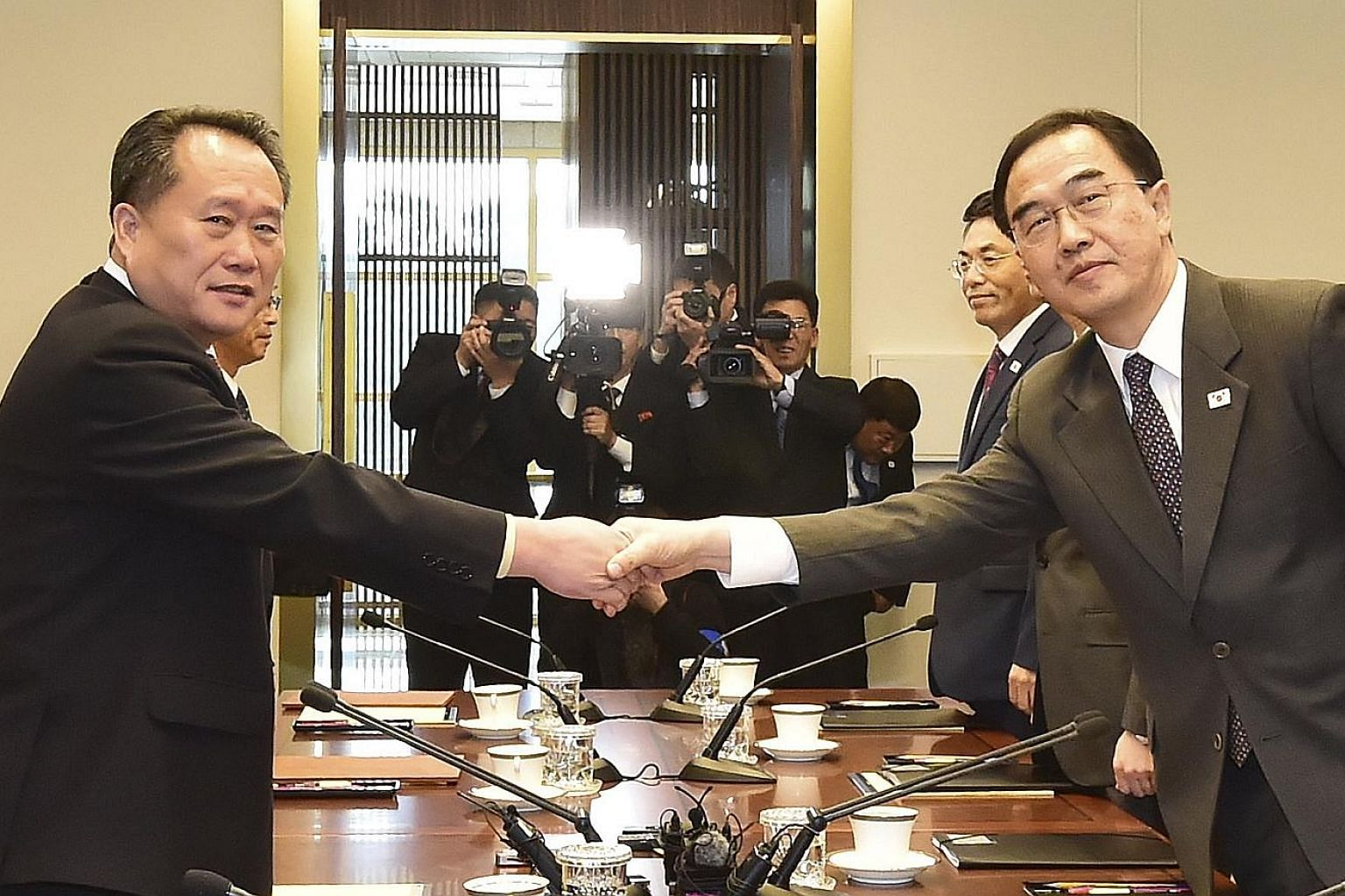 South Korean Unification Minister Cho Myoung-gyon (wearing glasses) and North Korea's Committee for Peaceful Reunification chairman Ri Son Gwon shaking hands prior to their talks in Panmunjom yesterday.