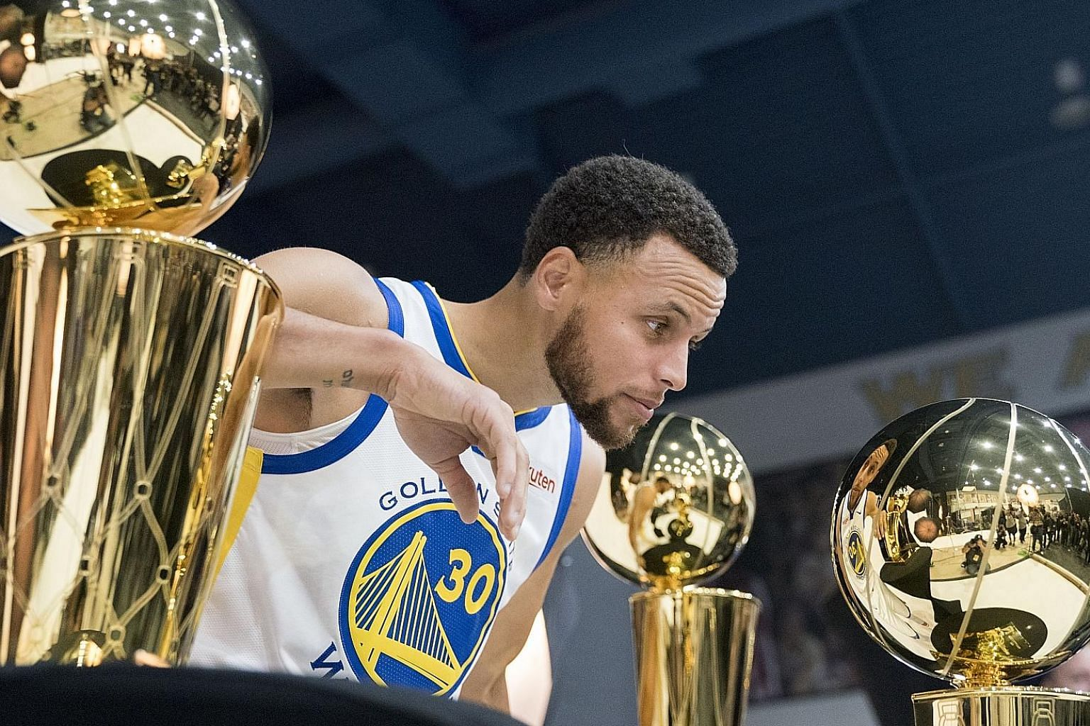 Golden State Warriors' star guard Stephen Curry in a pensive mood as he looks at the team's championship trophies during a media day at Rakuten Performance Centre last month.