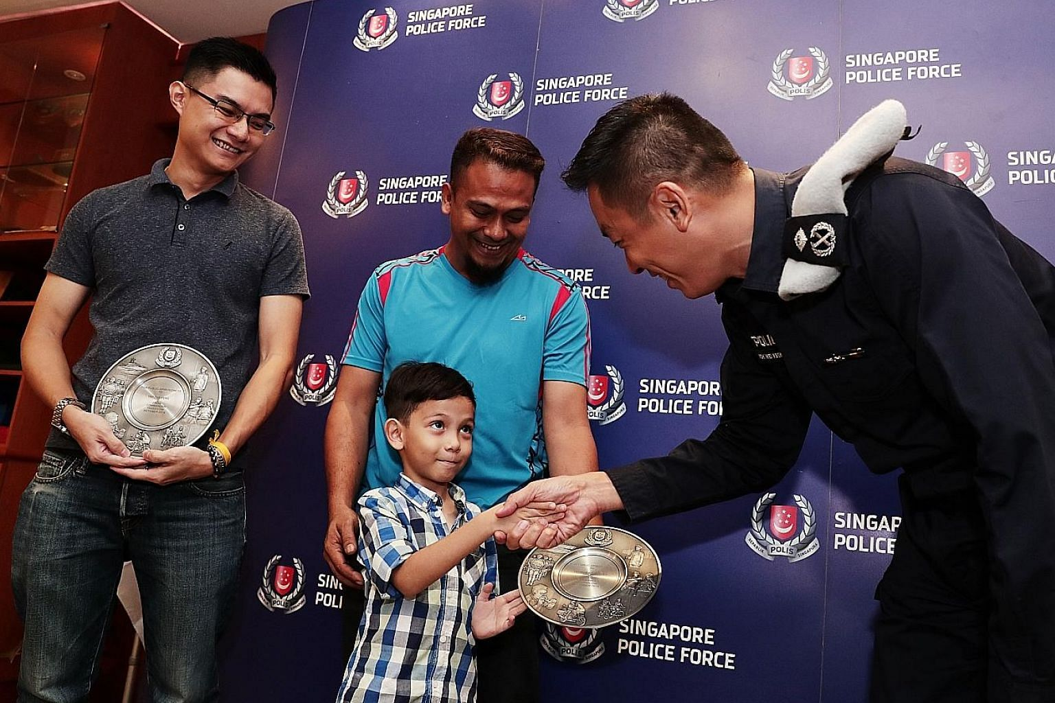 Five-year-old Mohd Ashqil, with his father Yusman Yusoff behind him, greeting Public Transport Security Command Commander Koh Wei Keong at the award ceremony yesterday. Mr Yusman and Mr Yap Zuo Peng (left) both received the Public Spiritedness Award