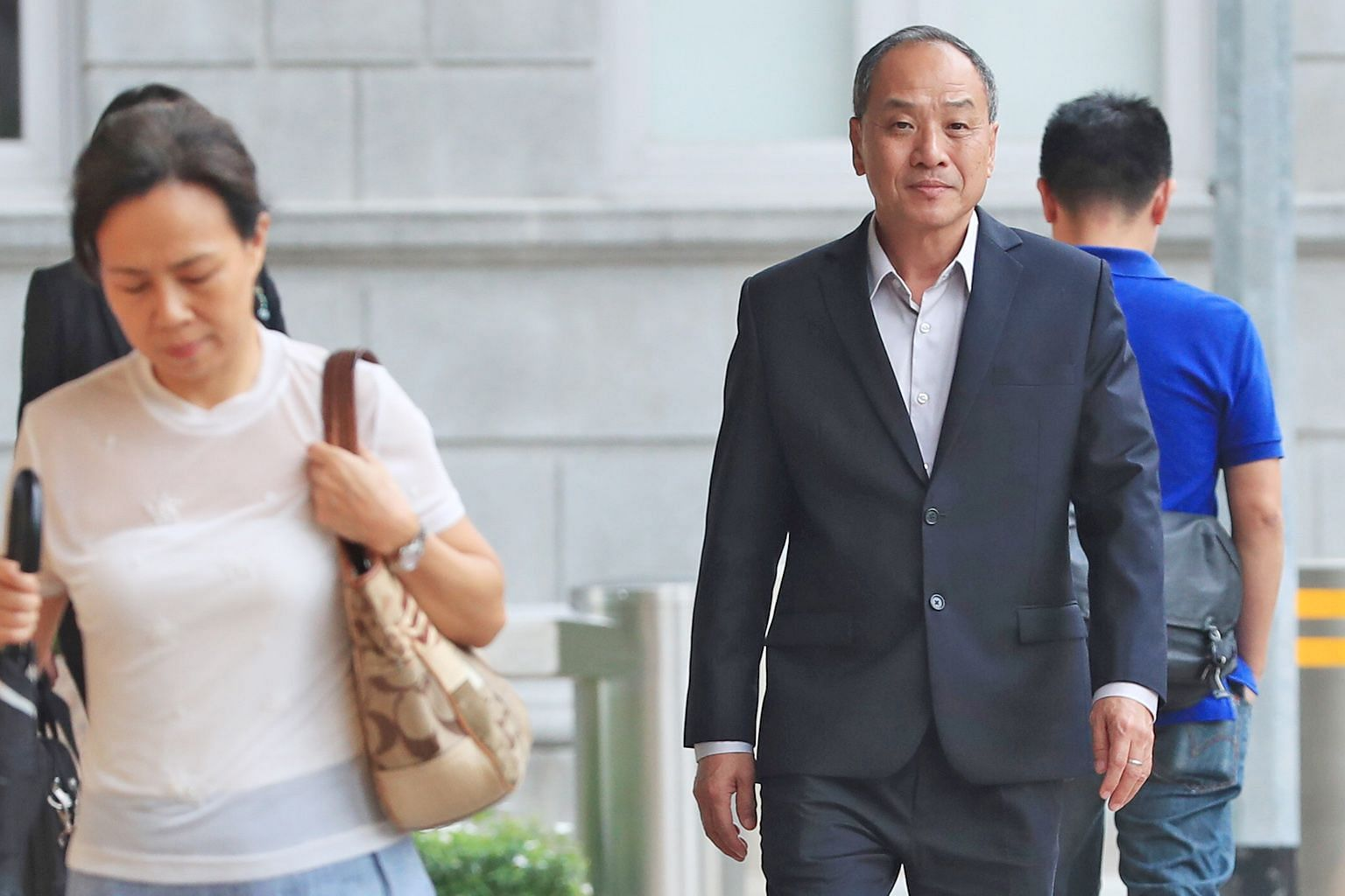 """Former Workers' Party chief Low Thia Khiang, seen here on his way to court yesterday, said it had not crossed his mind whether a tender should be called, and disagreed with Senior Counsel Davinder Singh that calling a tender would have """"upset the pla"""