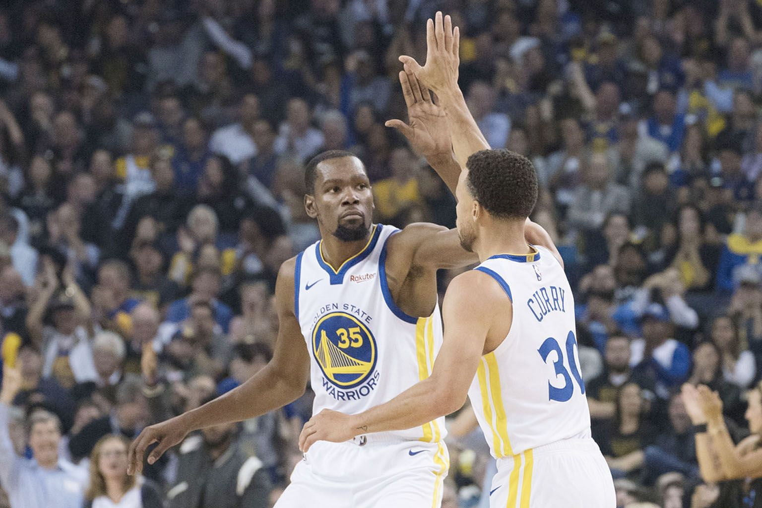 Golden State Warriors' Kevin Durant congratulating his teammate Stephen Curry for nailing a three-pointer during their 108-100 opening win over the Oklahoma City Thunder.