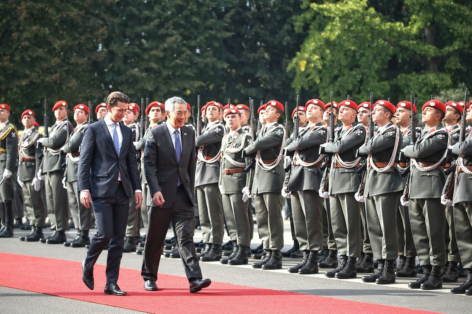 Austrian Chancellor Sebastian Kurz accompanying Prime Minister Lee Hsien Loong as he is welcomed by a military honour guard at the Federal Chancellery in Vienna yesterday. Both countries inked a pact to step up cooperation in digitalisation and infor